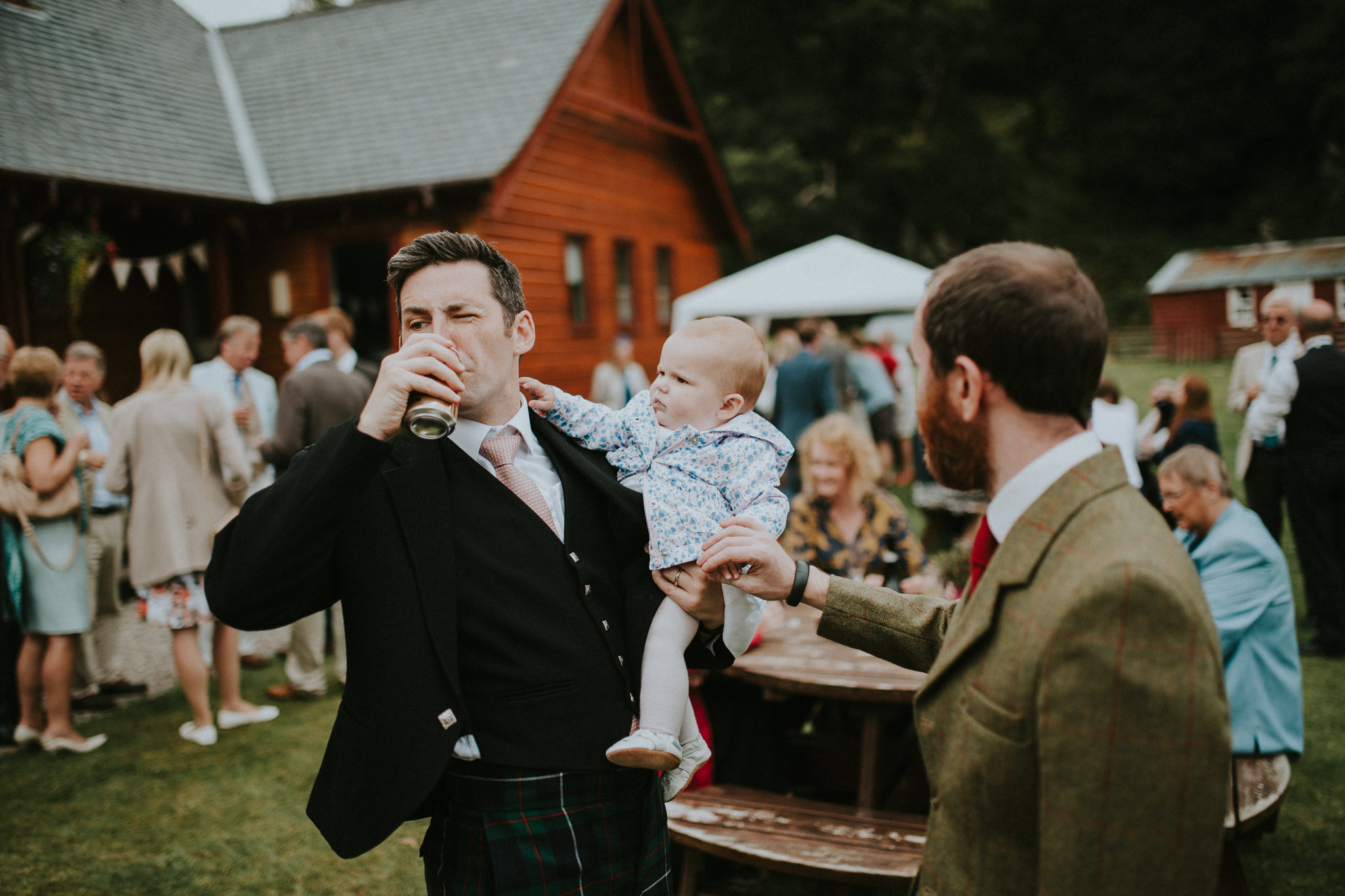 A wedding guest is holding a baby, drinking and standing next to another wedding guest.