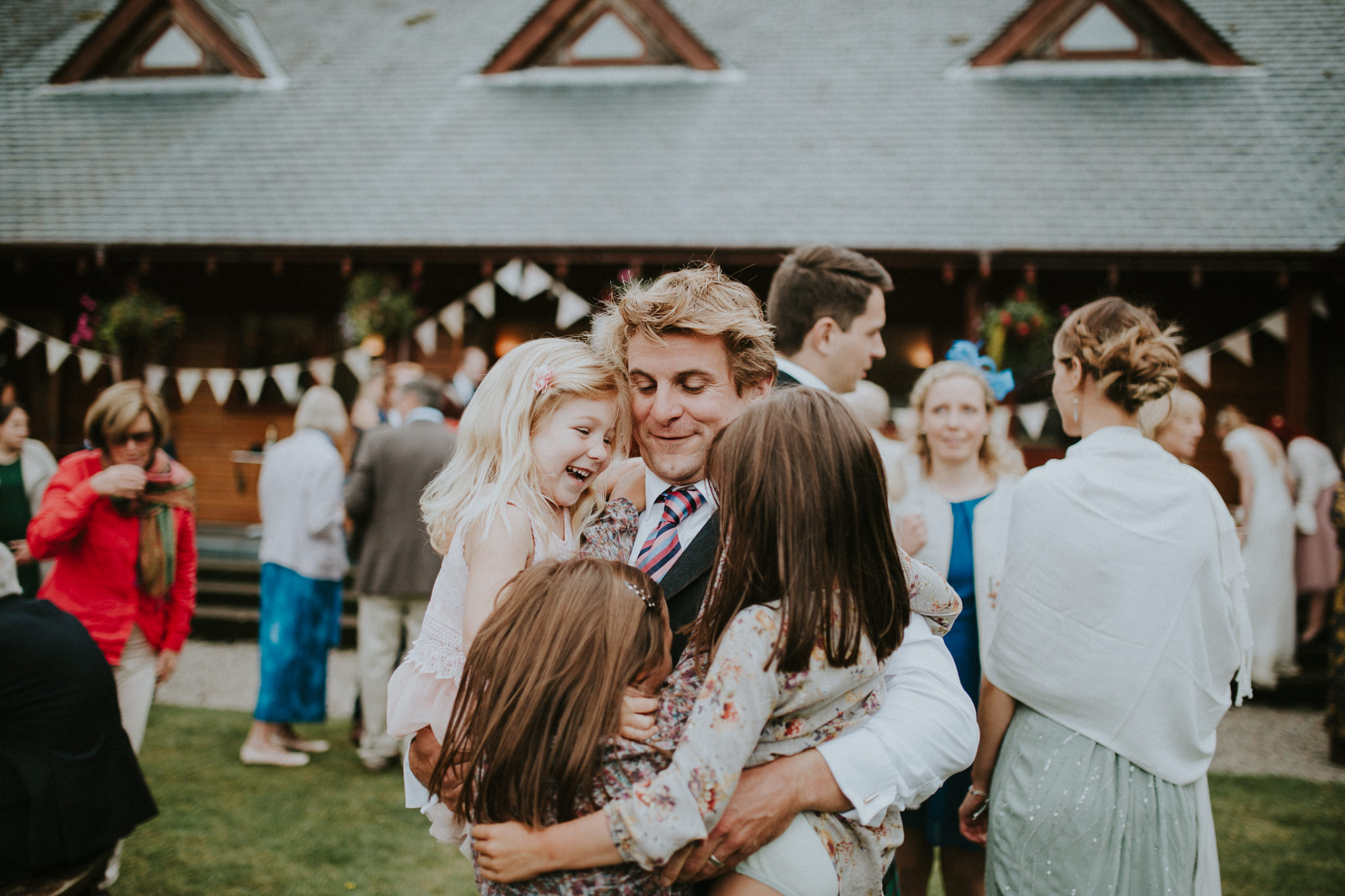 A wedding guest is hugging three children.
