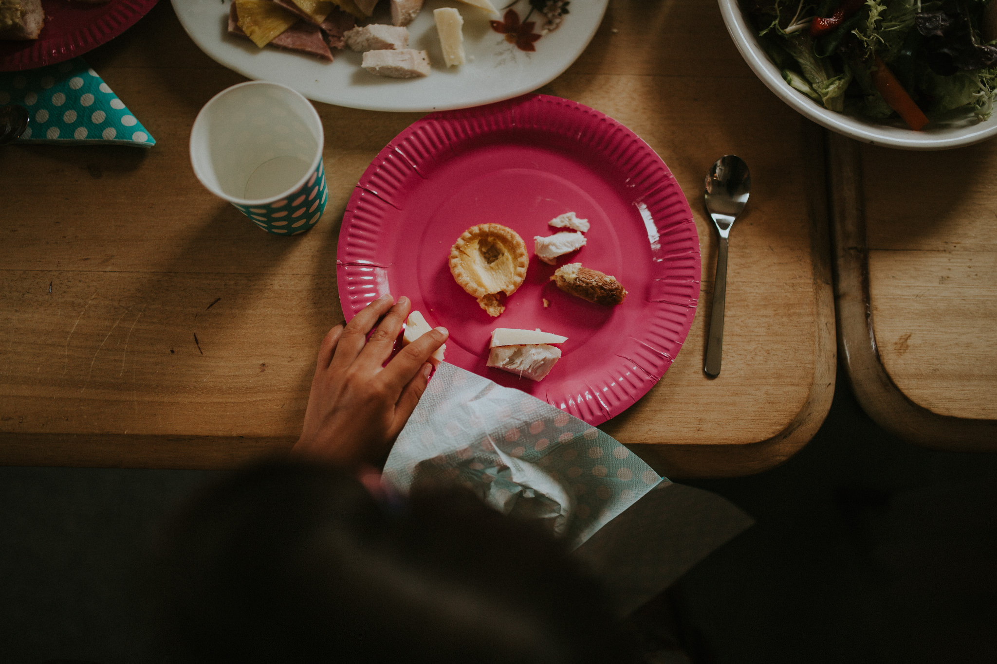 This closeup shows the pink plate of a wedding guests with some food on it.