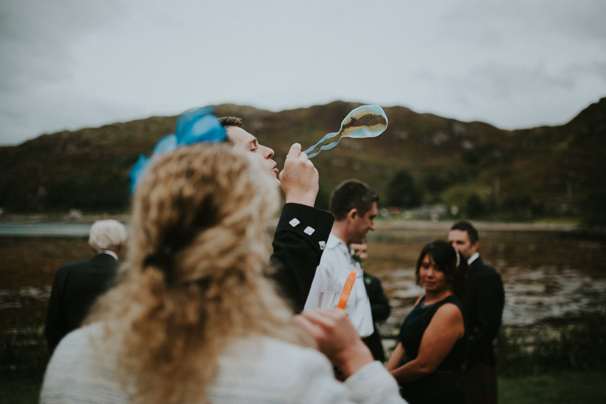 A wedding guest is blowing a soap bubble.