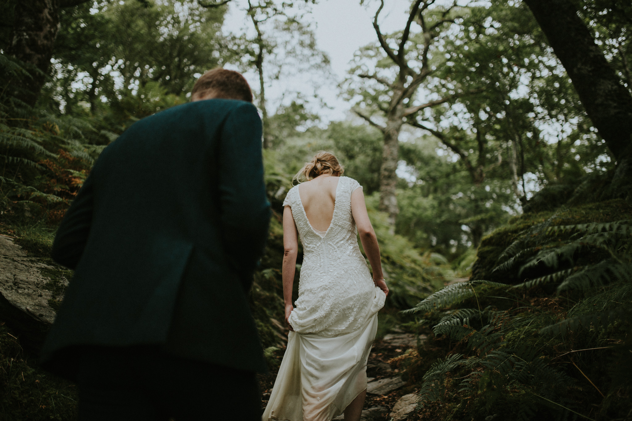 The wedding couple is hiking up a hill.
