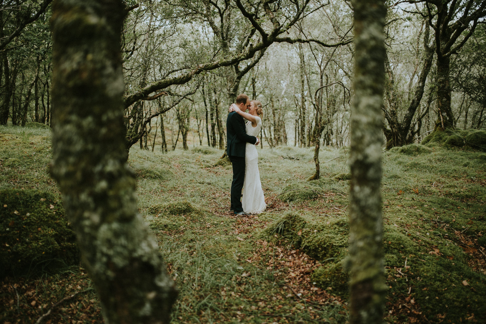 The wedding couple is holding each other in the forest.