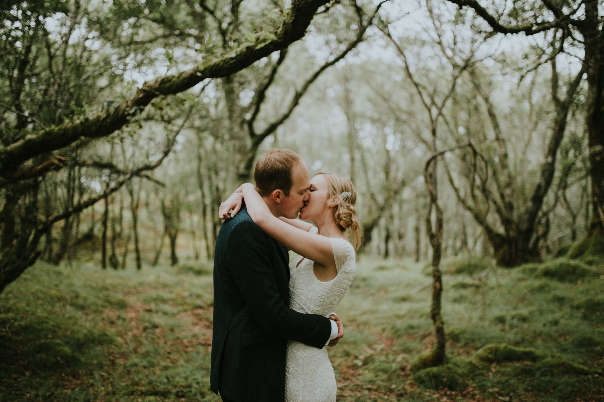 The wedding couple is kissing each other in the forest.