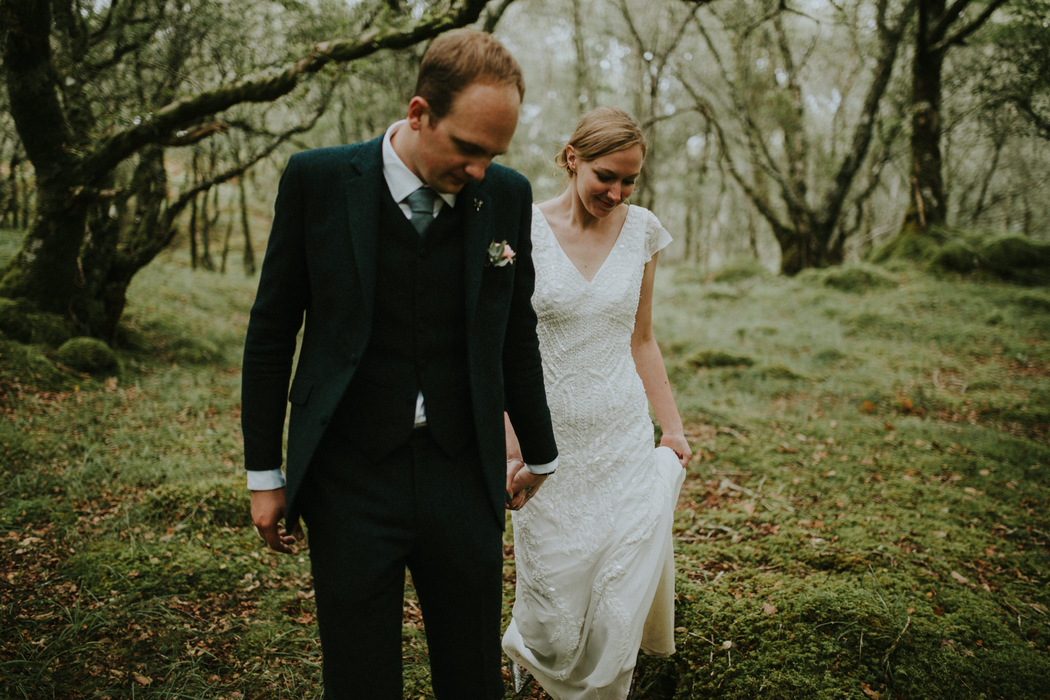 The wedding couple is holding hands and walking through the forest.