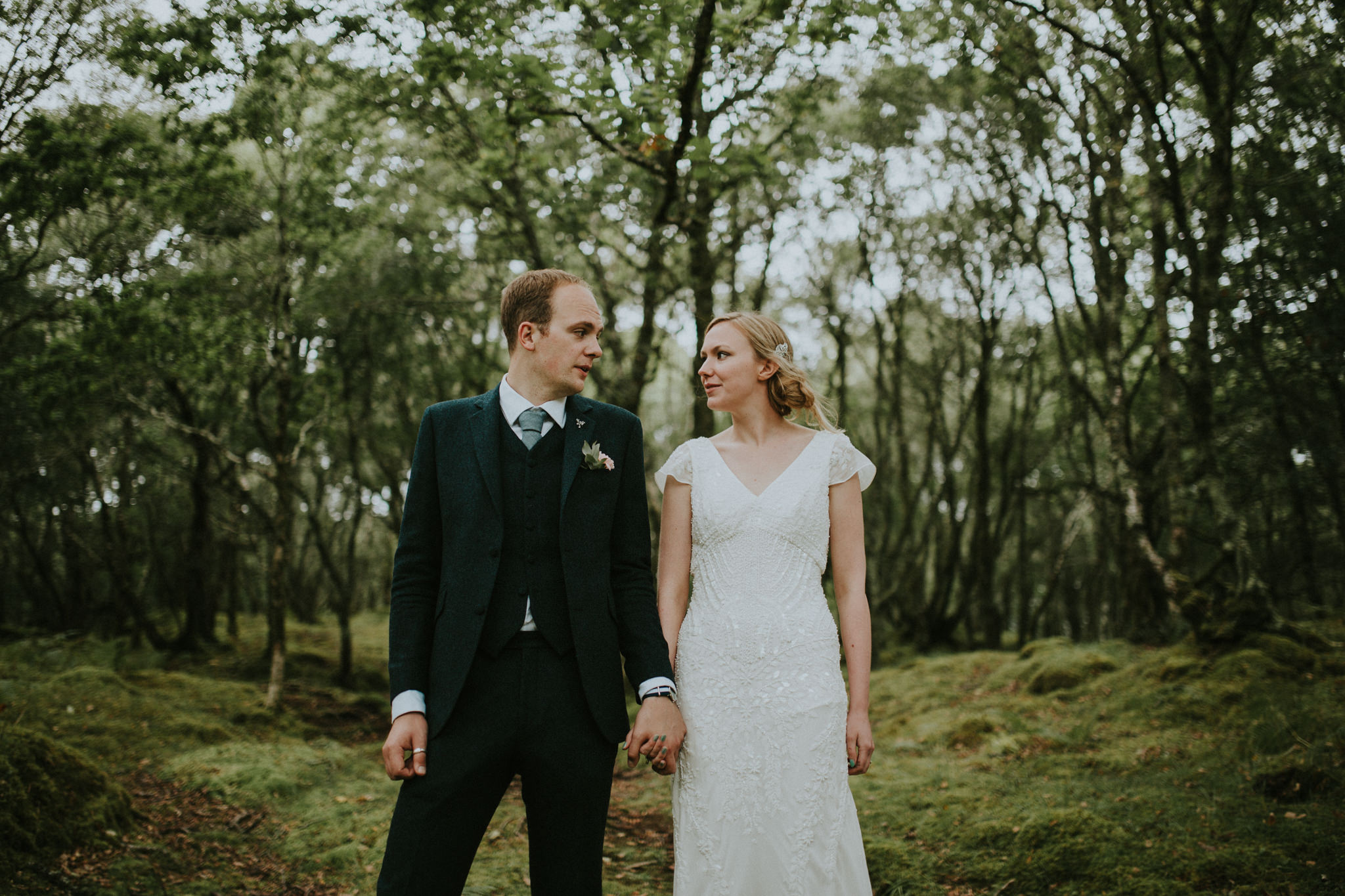The wedding couple is holding hands and standing in the middle of a forest.