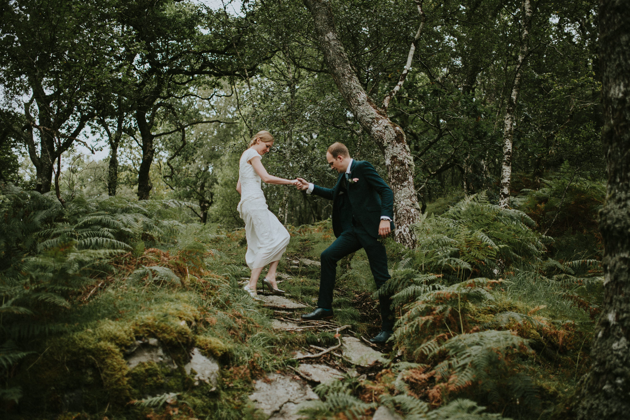 The groom is helping his bride through the forest.