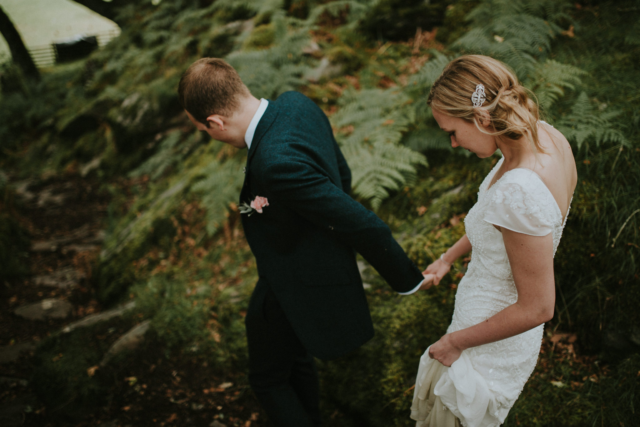 The wedding couple is walking down a hill in the forest.