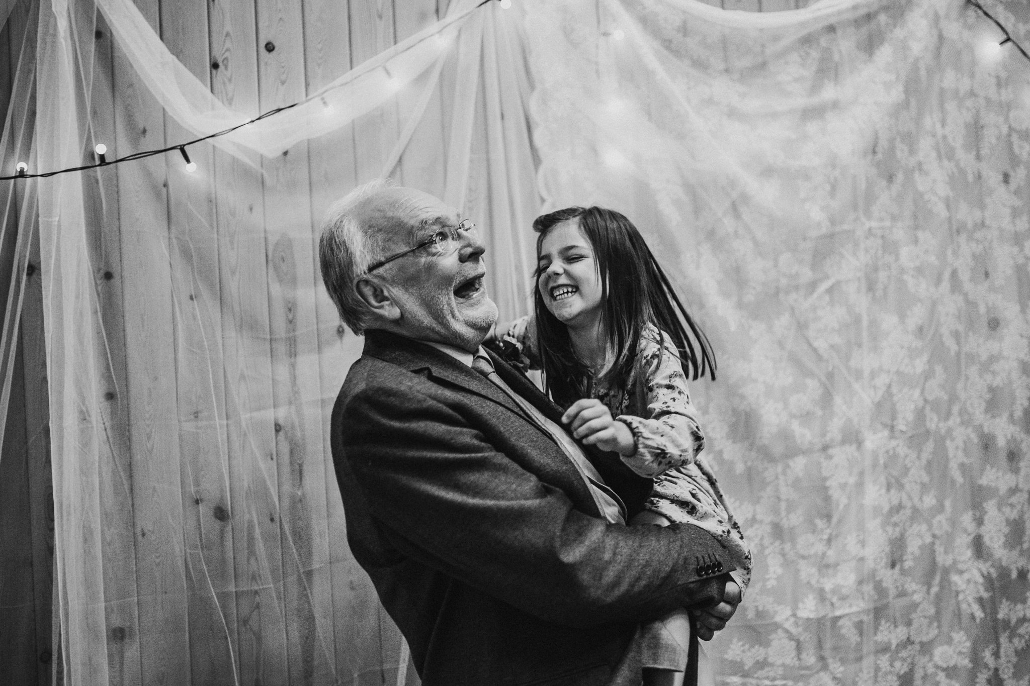 An old man is holding a little girl and they are laughing with each other.