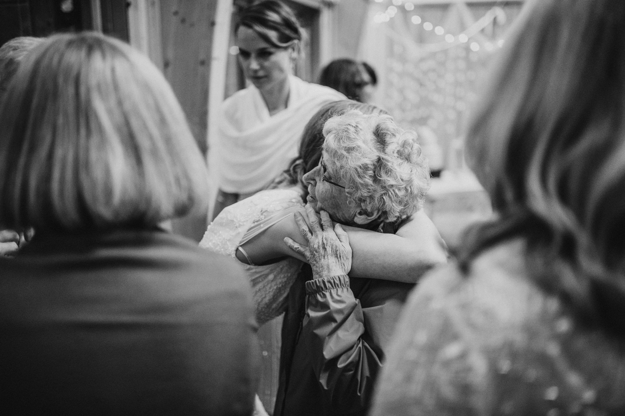 A wedding guest is hugging the bride.