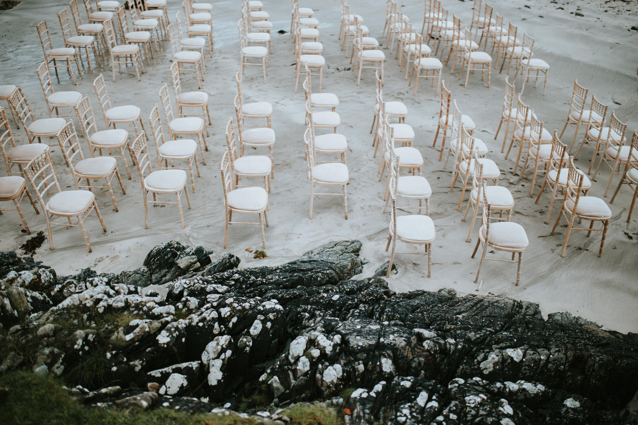 Chairs are lined up at the beach for the wedding ceremony.