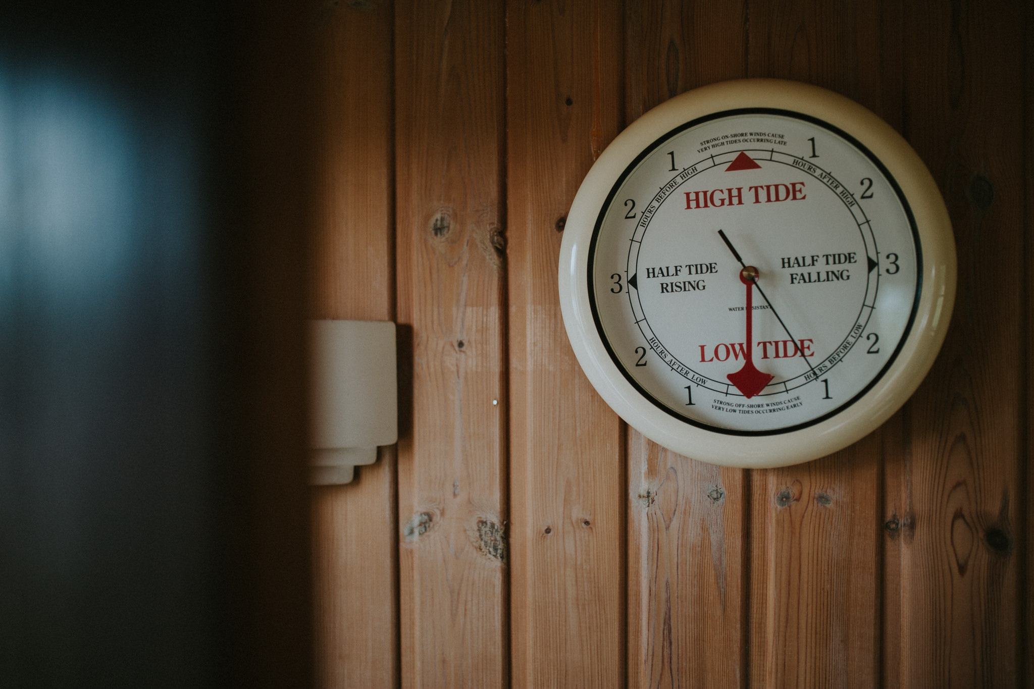 A tide indicator is attached to the wooden wall of the cottage.