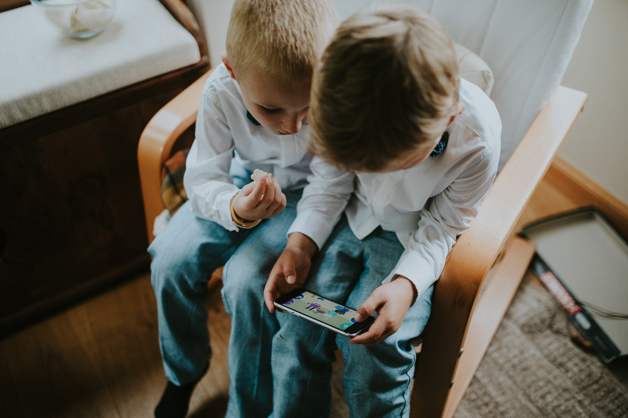 Two boys are sitting on a chair and looking at a mobile phone.