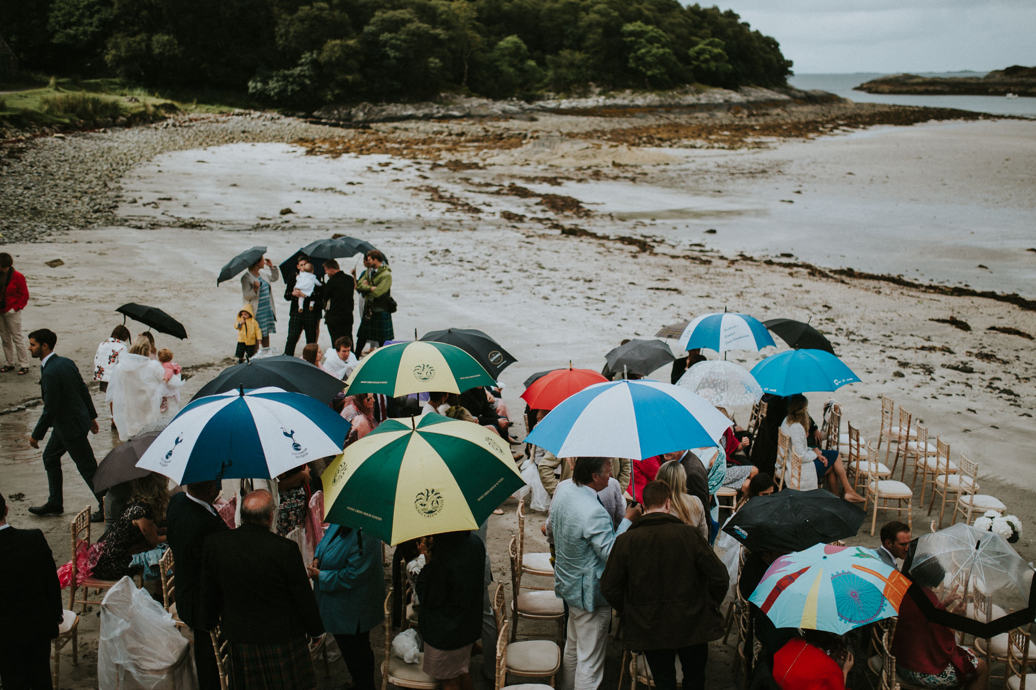 The wedding guests are standing at the beach and holding umbrellas.