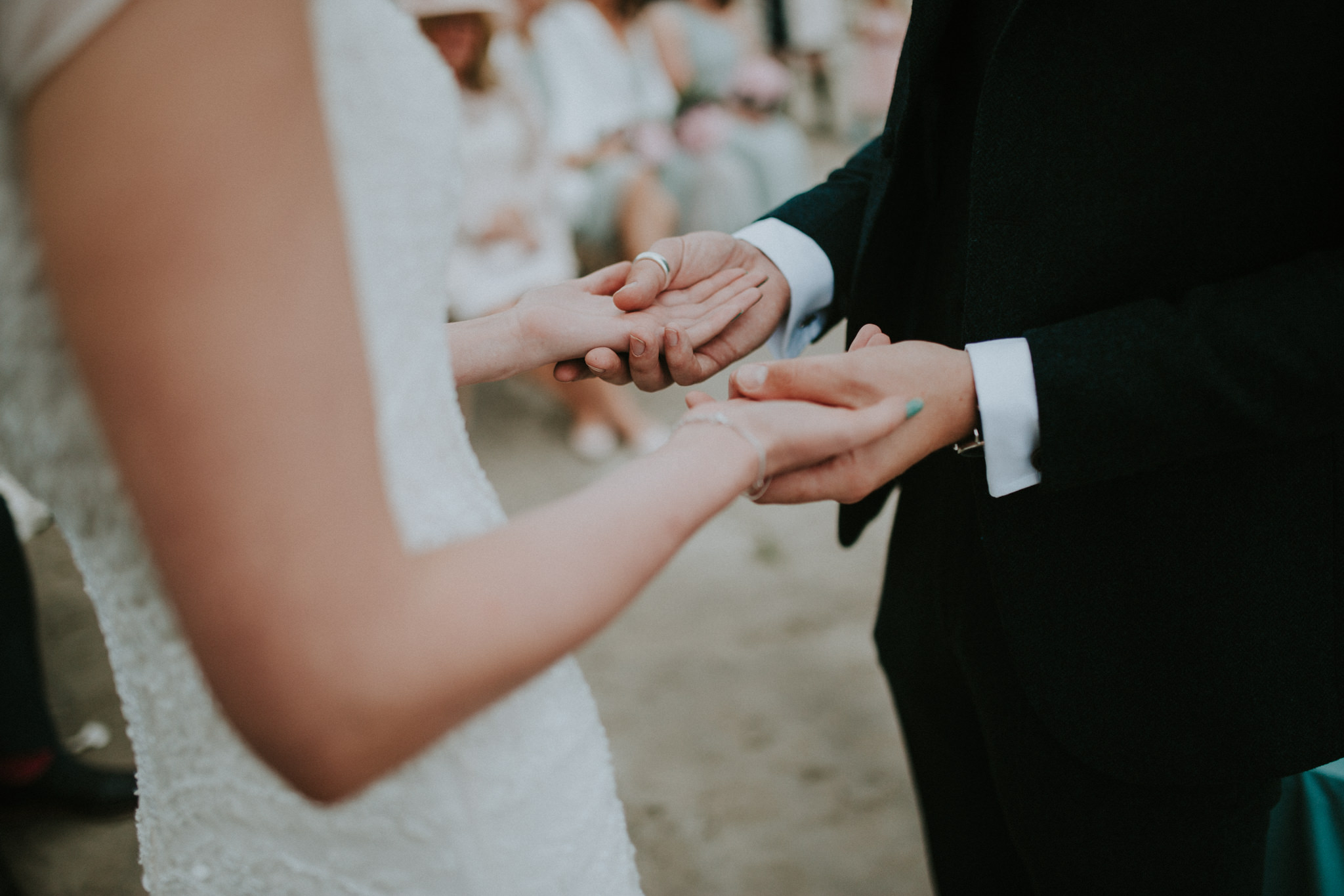 The groom is holding his brides hands.