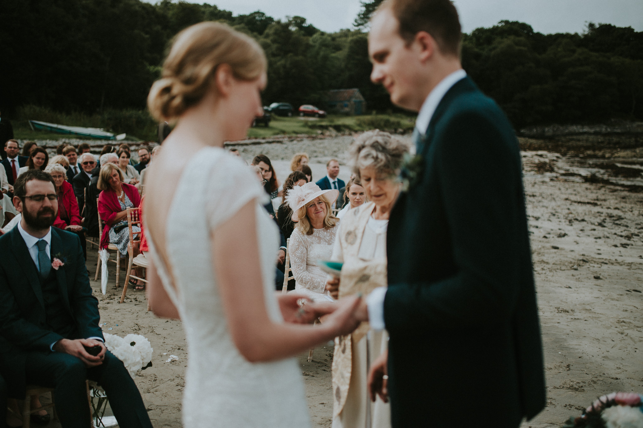 The wedding couple is standing in front of their guests and is holding hands.