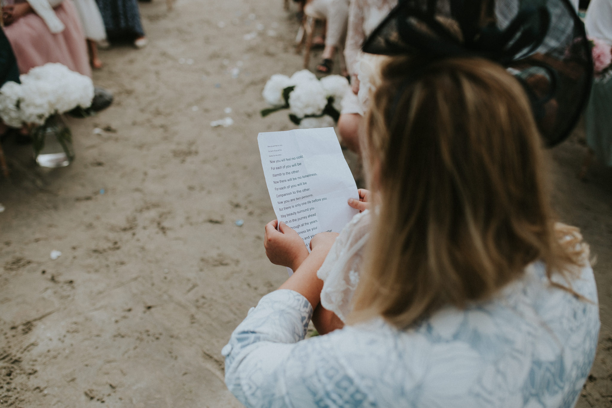 A wedding guest is holding a piece of paper.