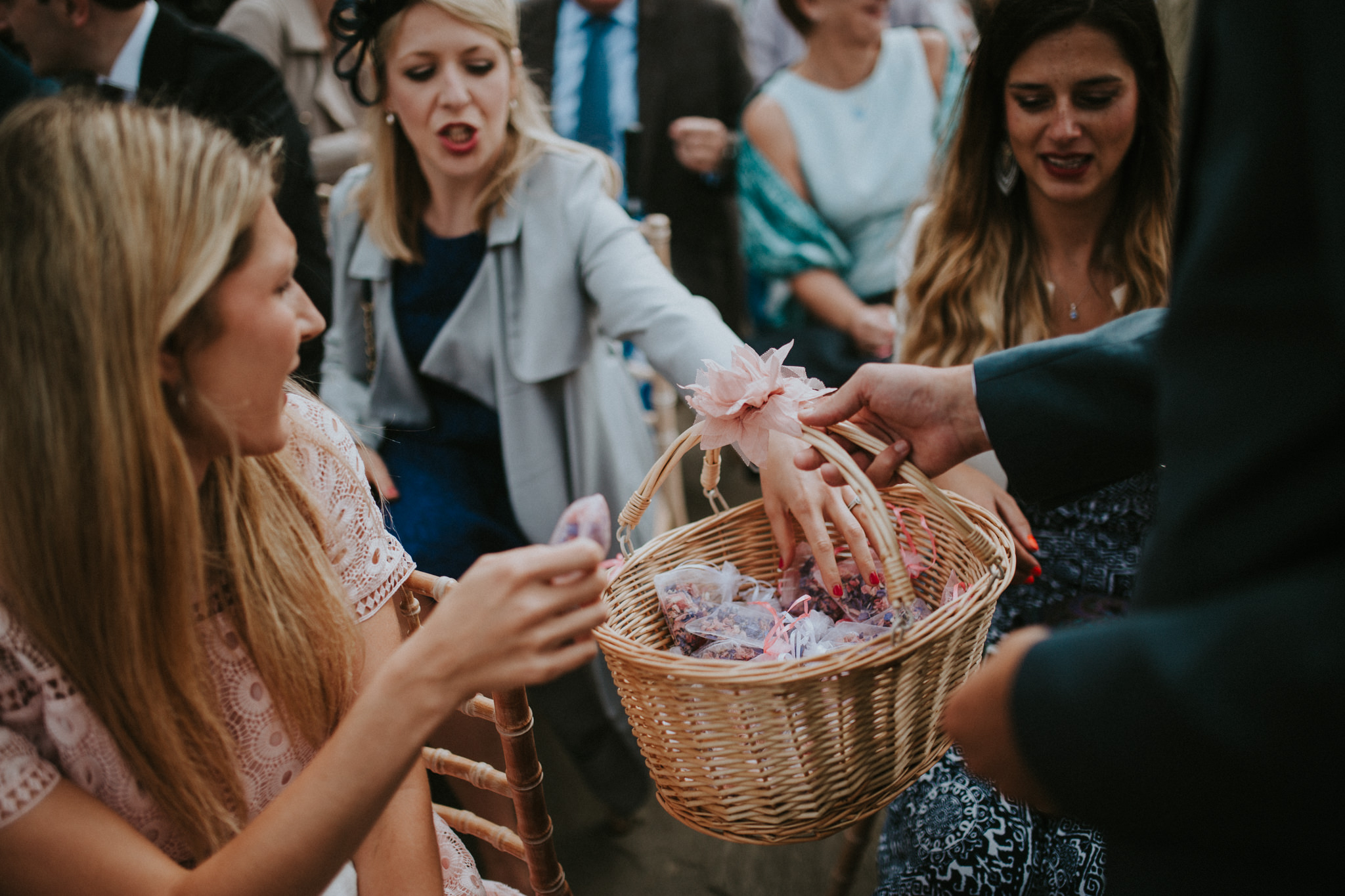 Wedding guests are taking rose petals out of a basket.