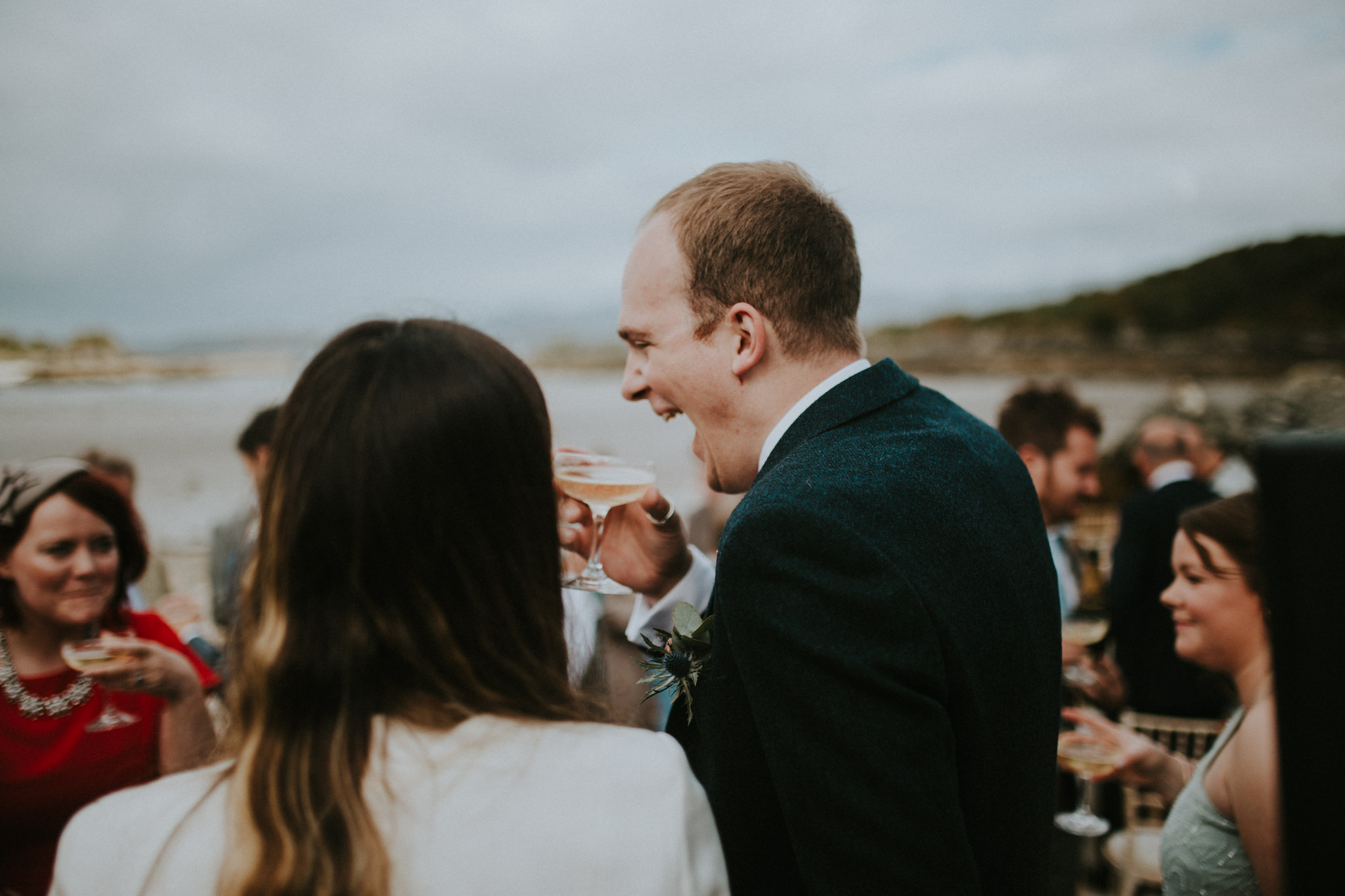 The groom is standing next to his guests and is laughing.