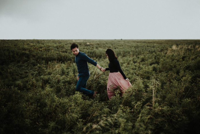 A couple is holding hands and walking through a meadow after an Iceland Proposal.
