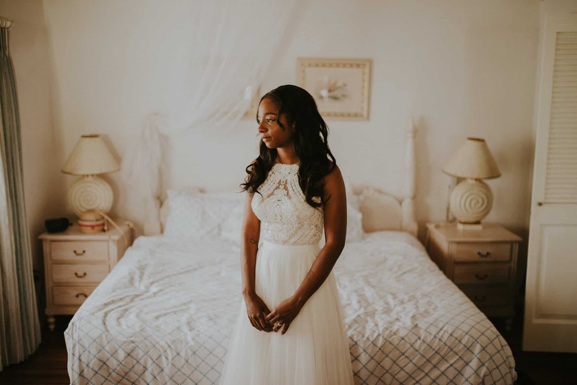 The bride is wearing her wedding dress and is standing in front of a bed.