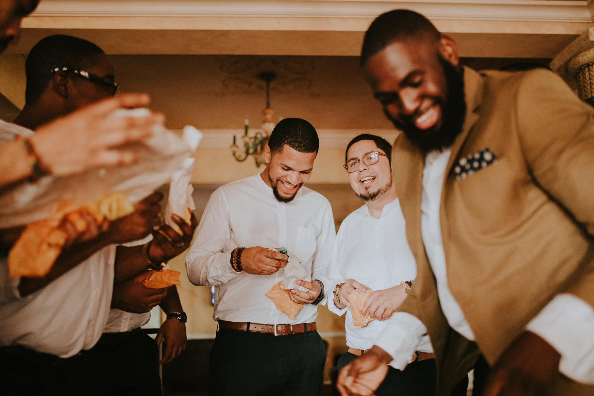 The groom is laughing with his groomsmen as they are unpacking presents.