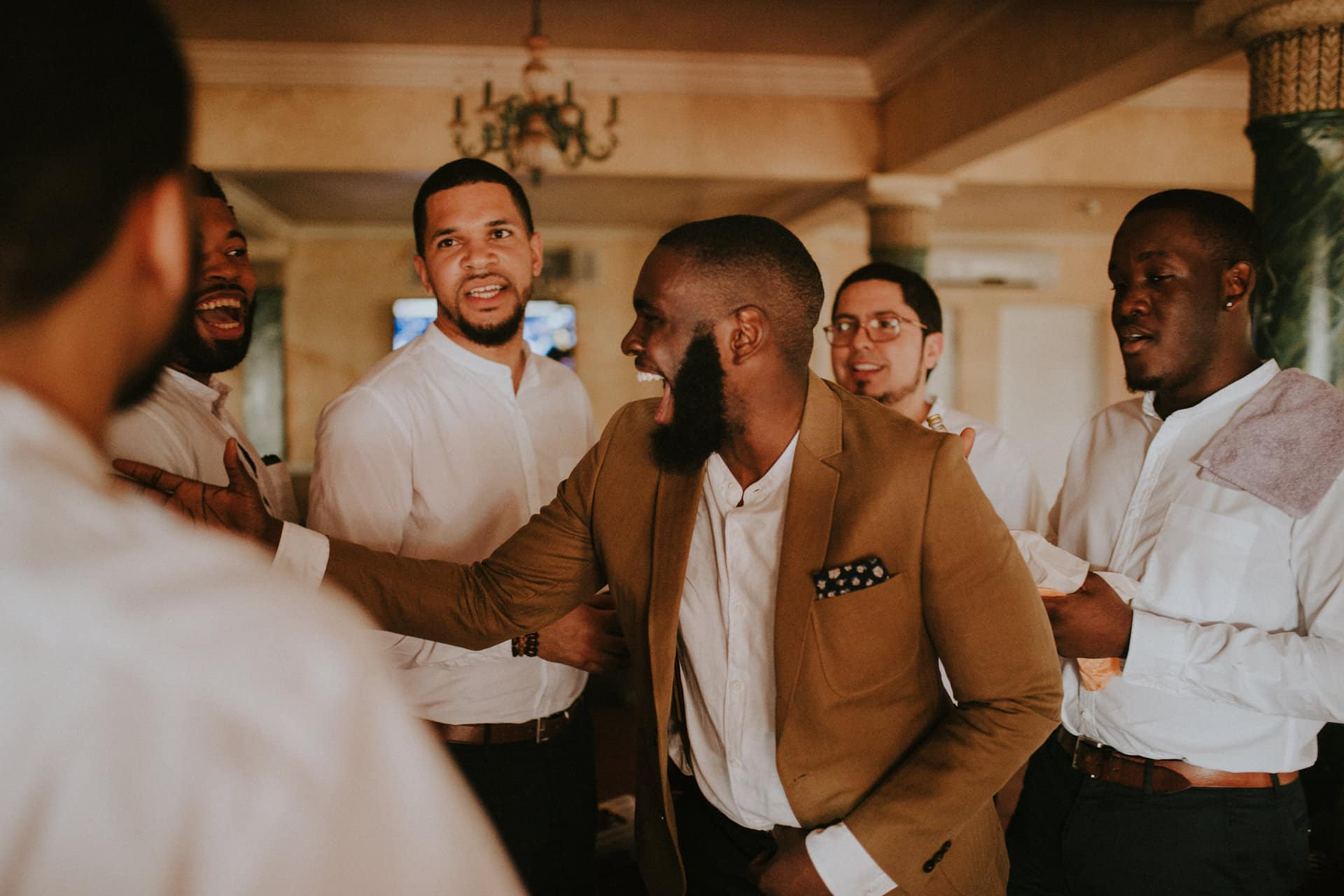 The groom is laughing with his groomsmen.