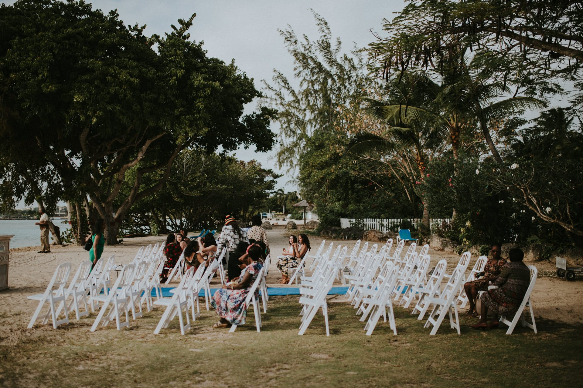 Wedding guests are sitting on chairs at the beach.