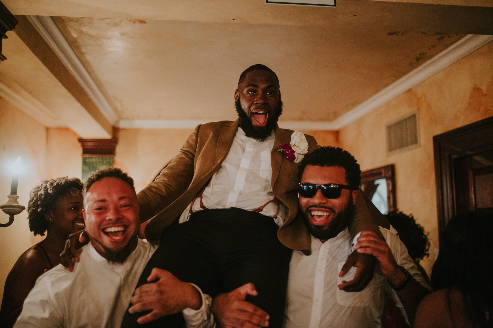 Two groomsmen are holding up the groom.