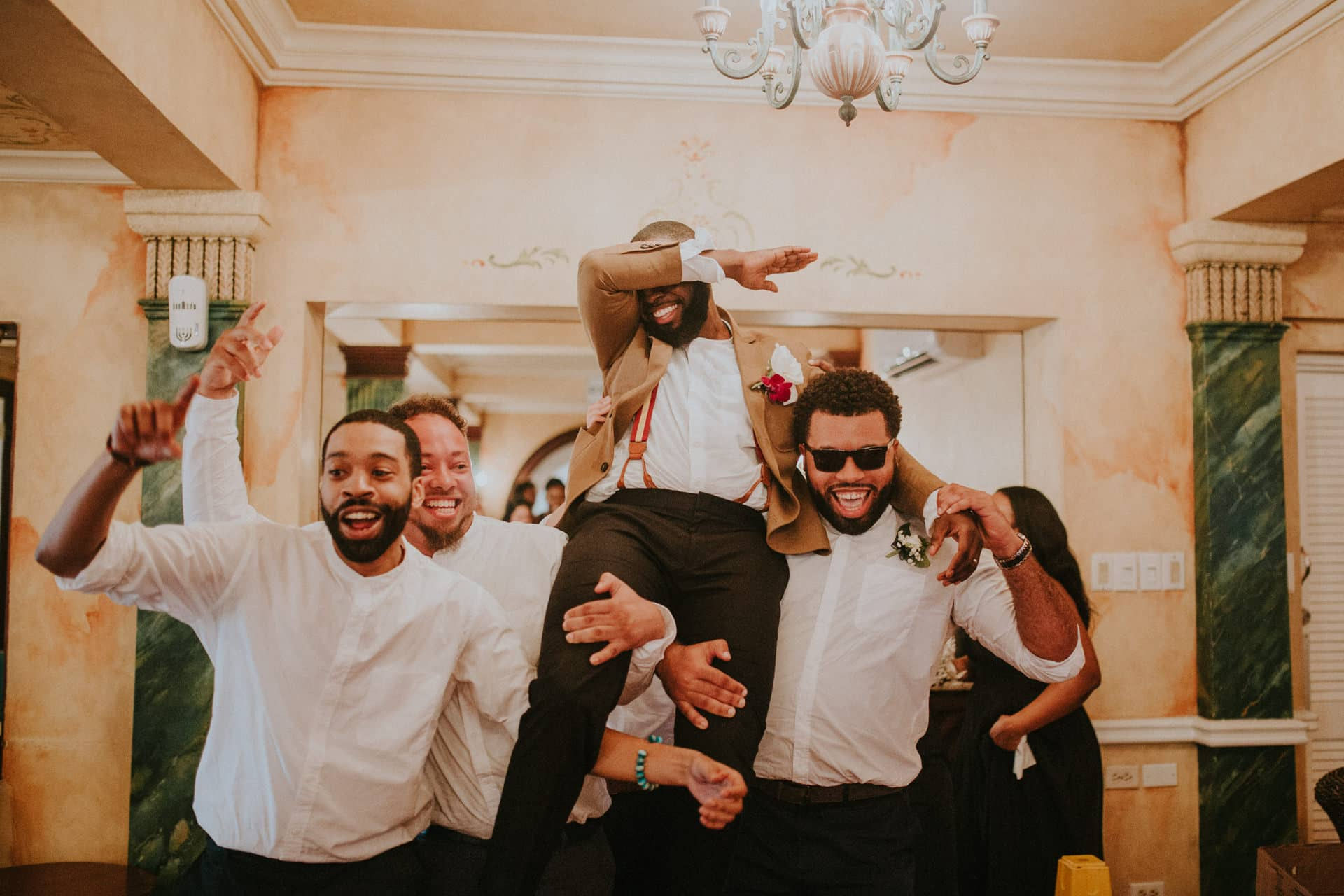 Groomsmen are holding up the groom.