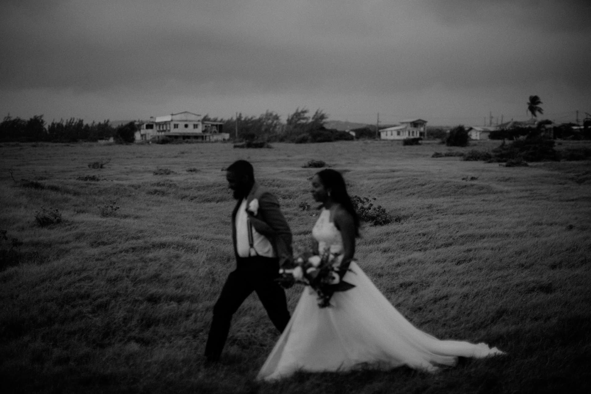 The wedding couples walking through a meadow.