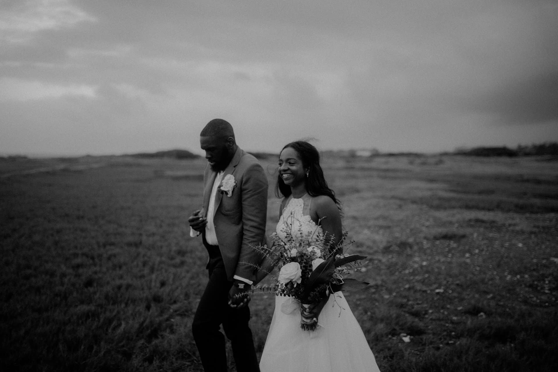 A wedding couple is walking through a meadow.