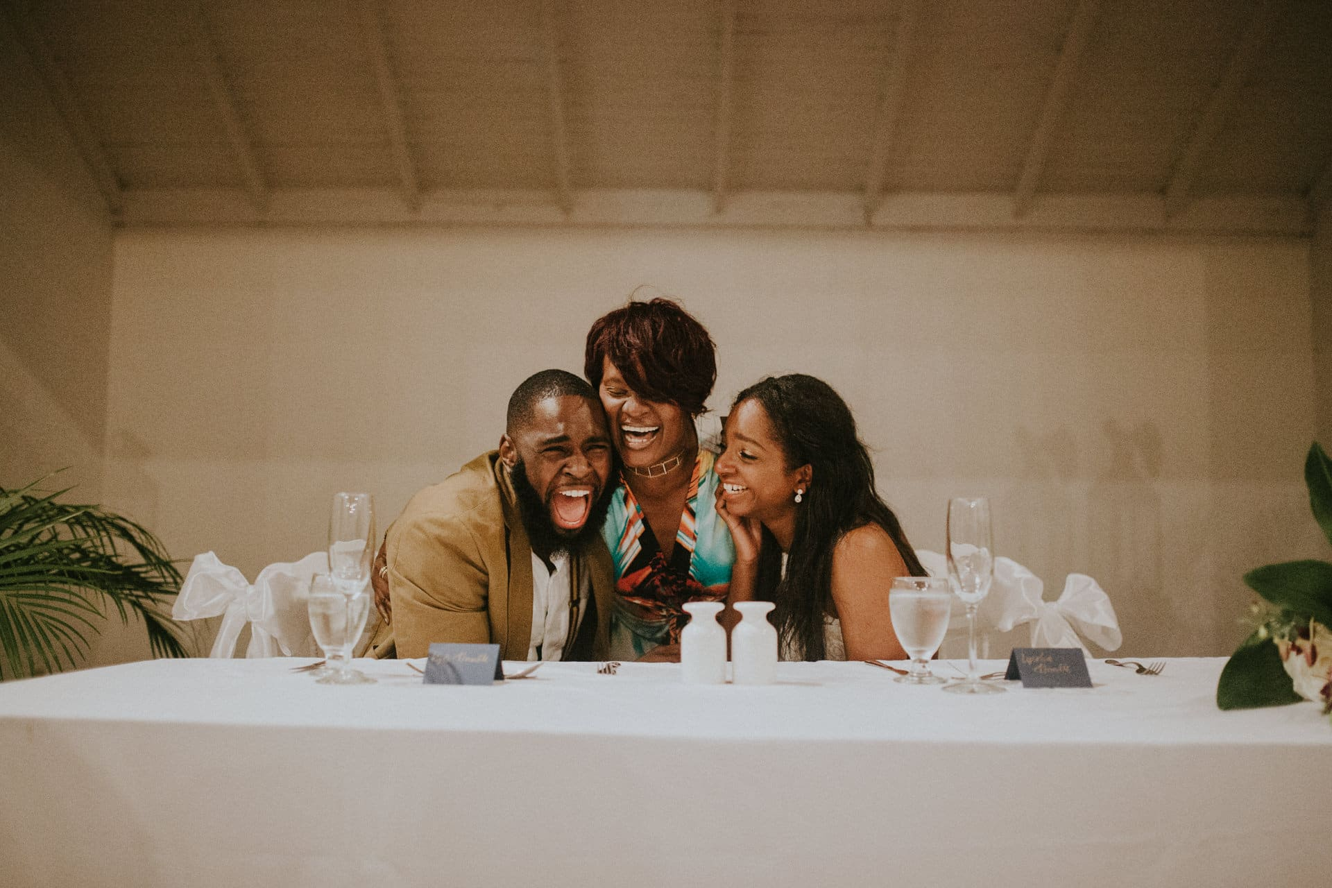 The wedding couple and a guest are laughing and sitting at the wedding table.