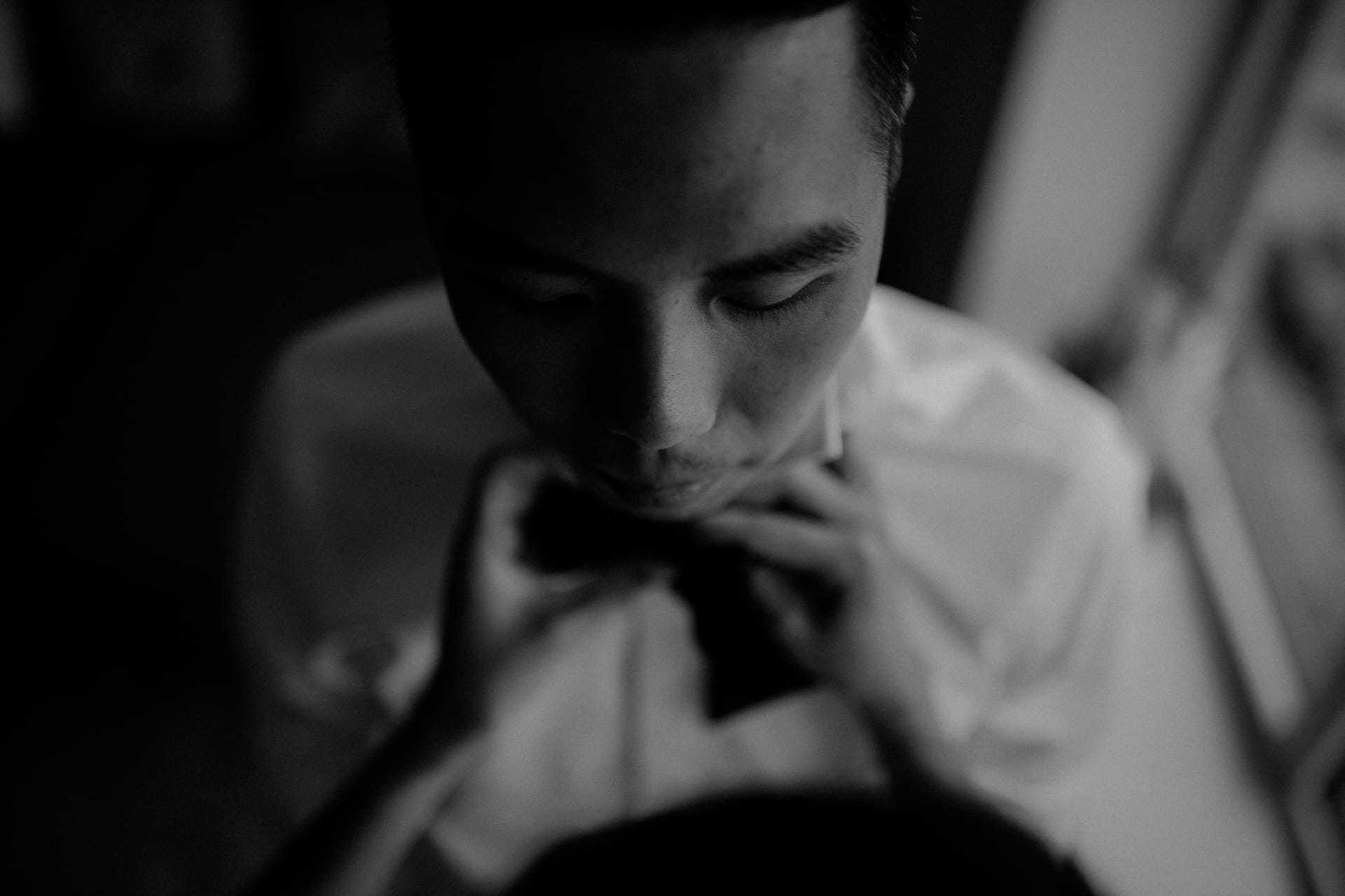 This closeup shows the groom getting his bow tie tied.