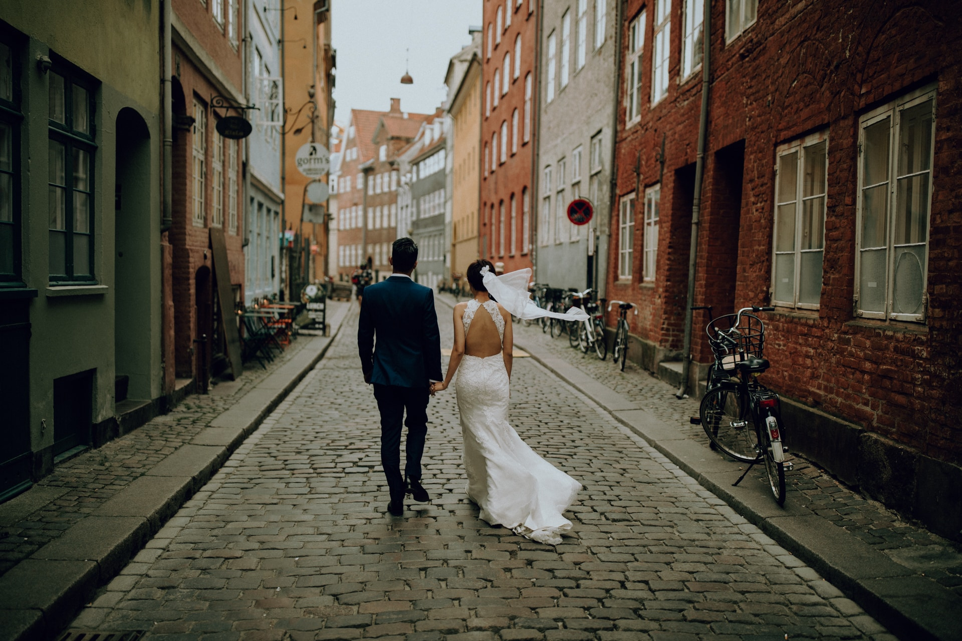 The wedding couple is walking through the old town of Copenhagen.