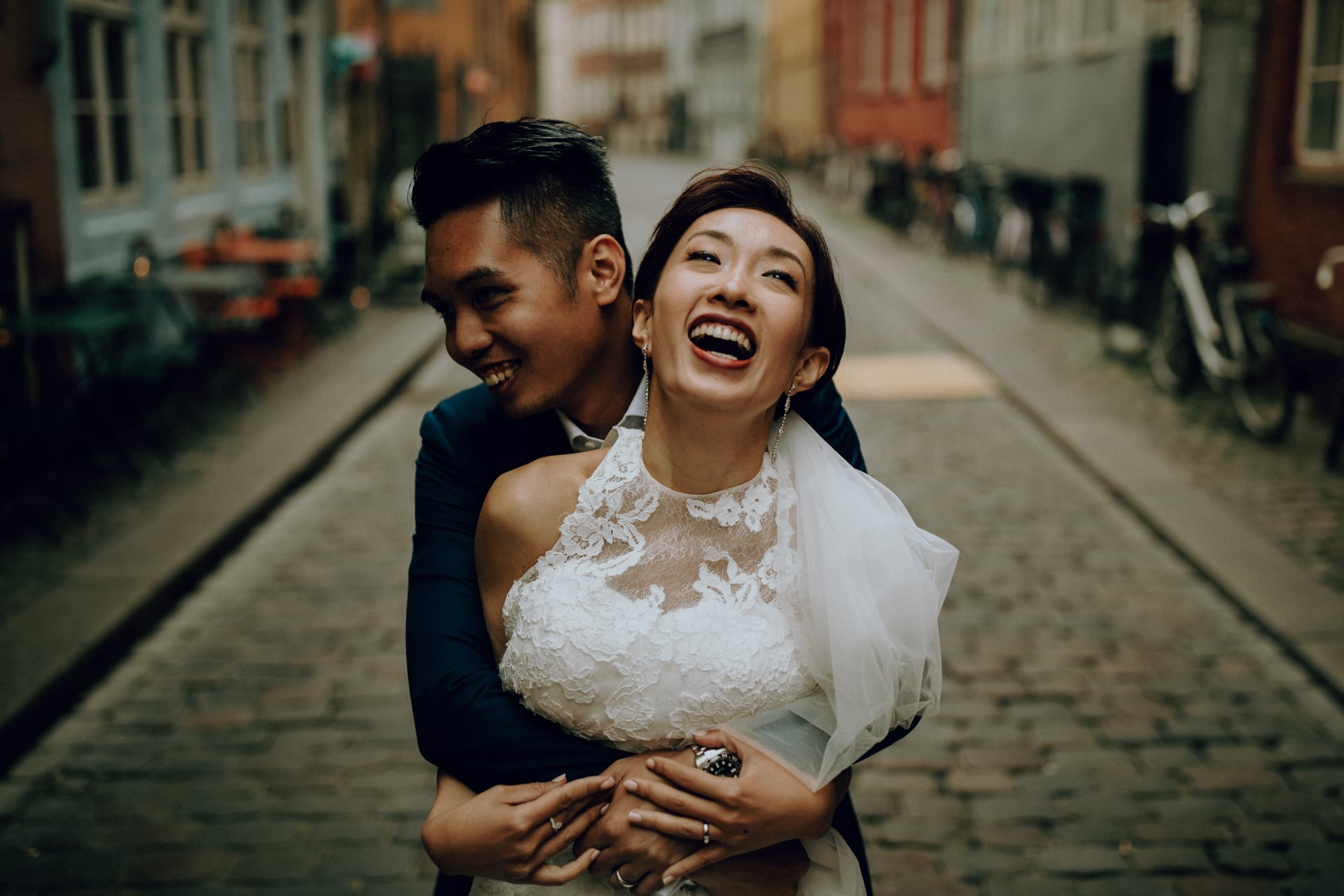 The groom is hugging his bride in the streets of Copenhagen.