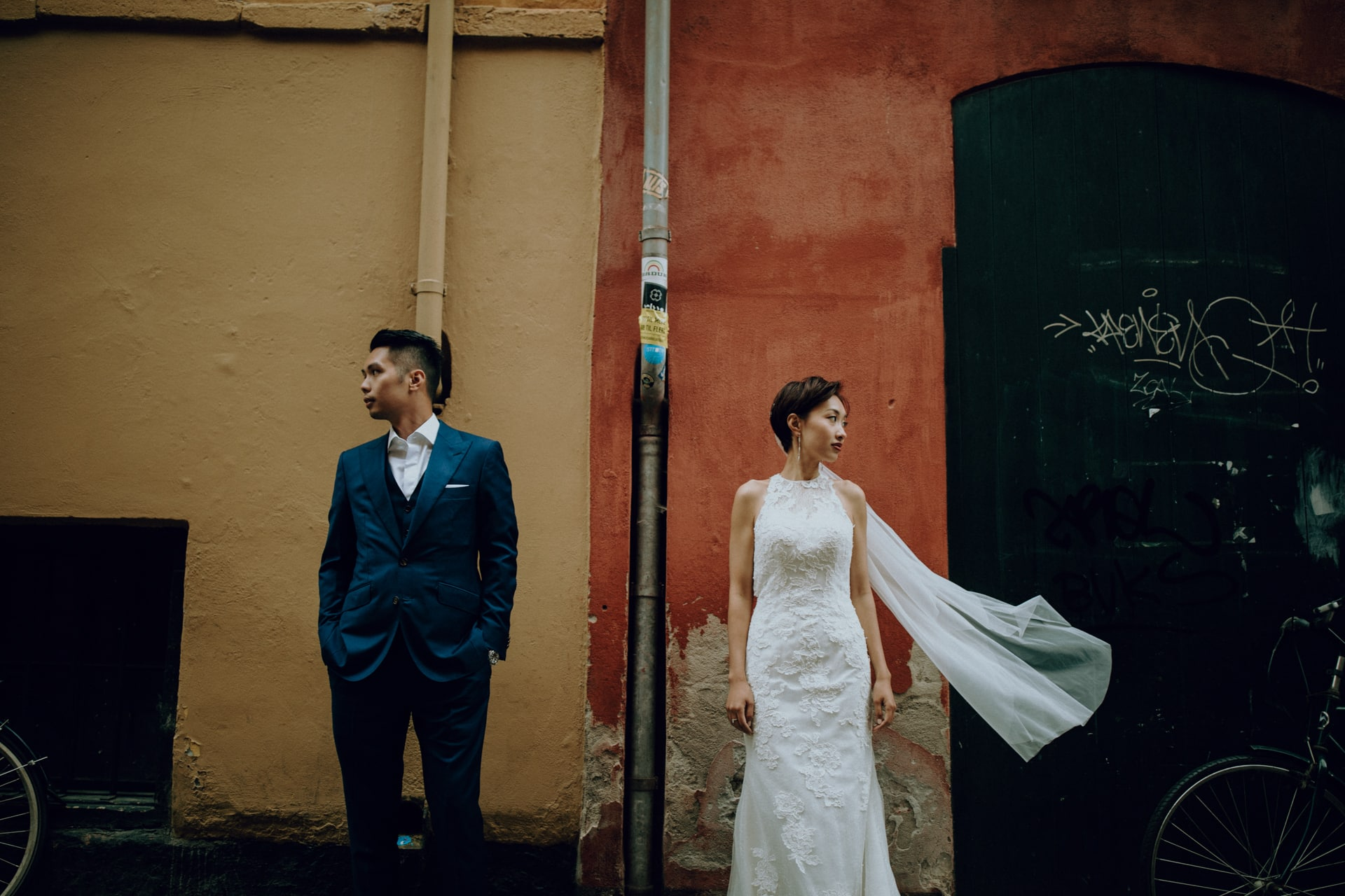 The wedding couple is standing in front of a orange and beige wall.