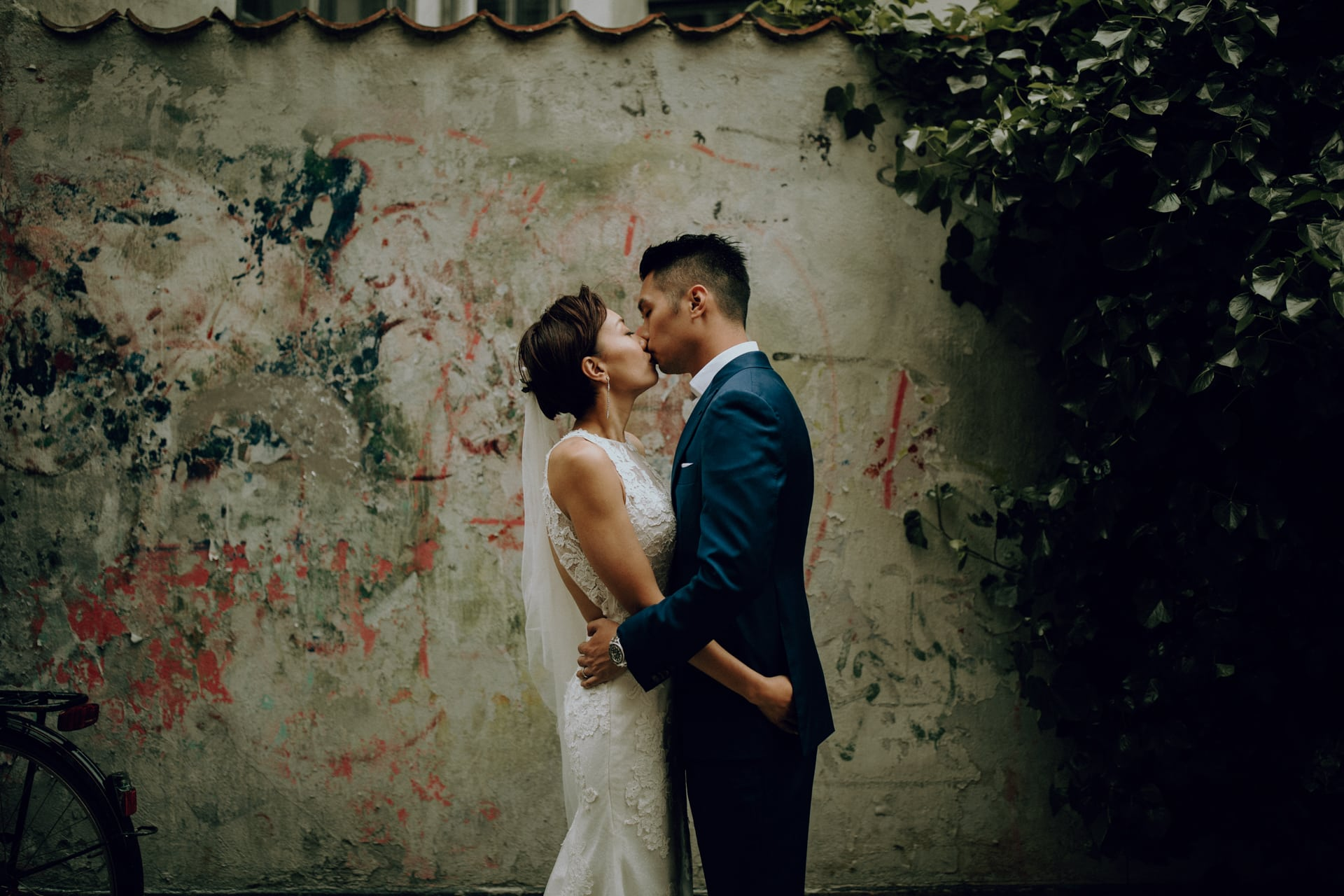 The wedding couple is kissing each other in front of an old wall.