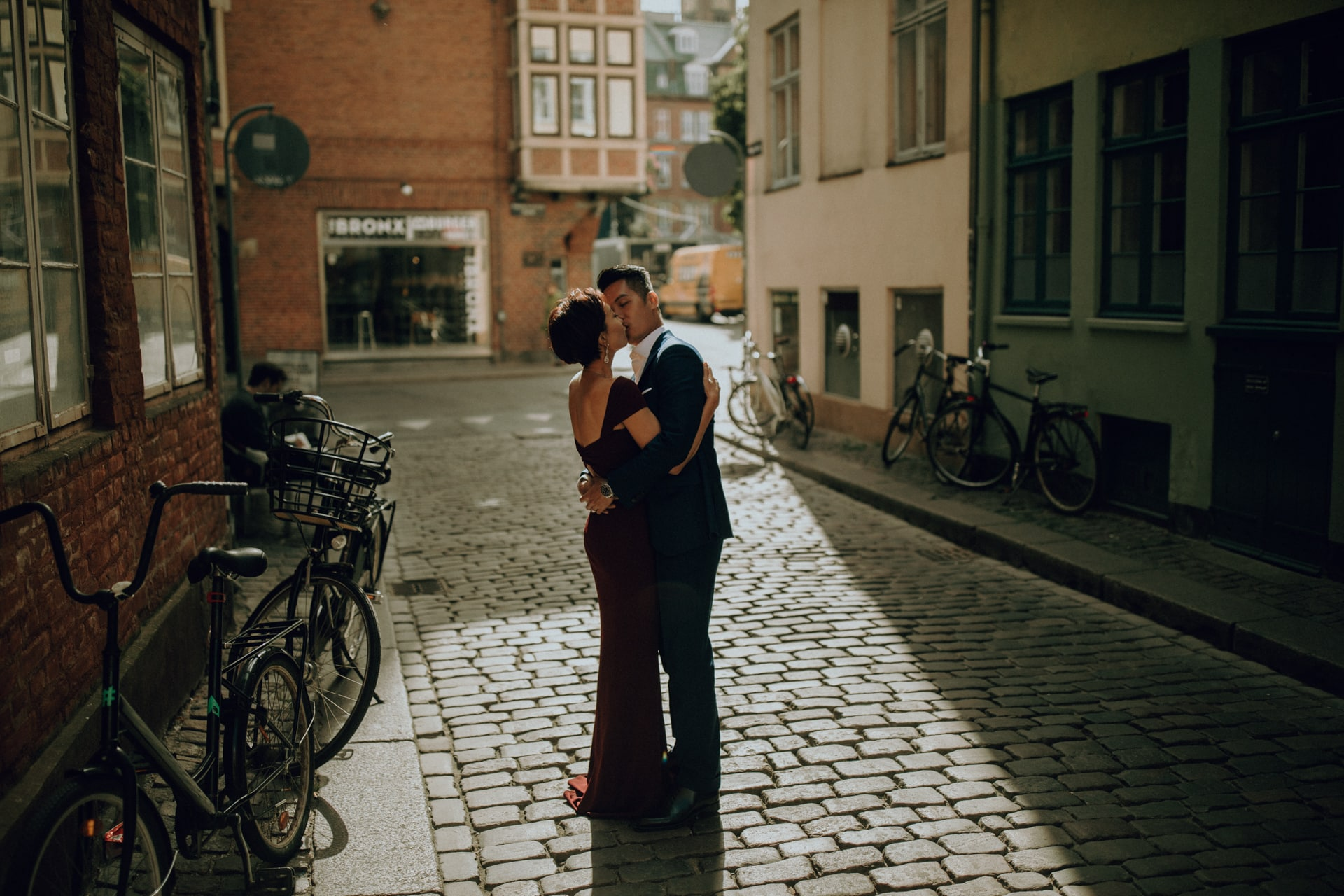 The wedding couple is kissing each other in the streets of Copenhagen.