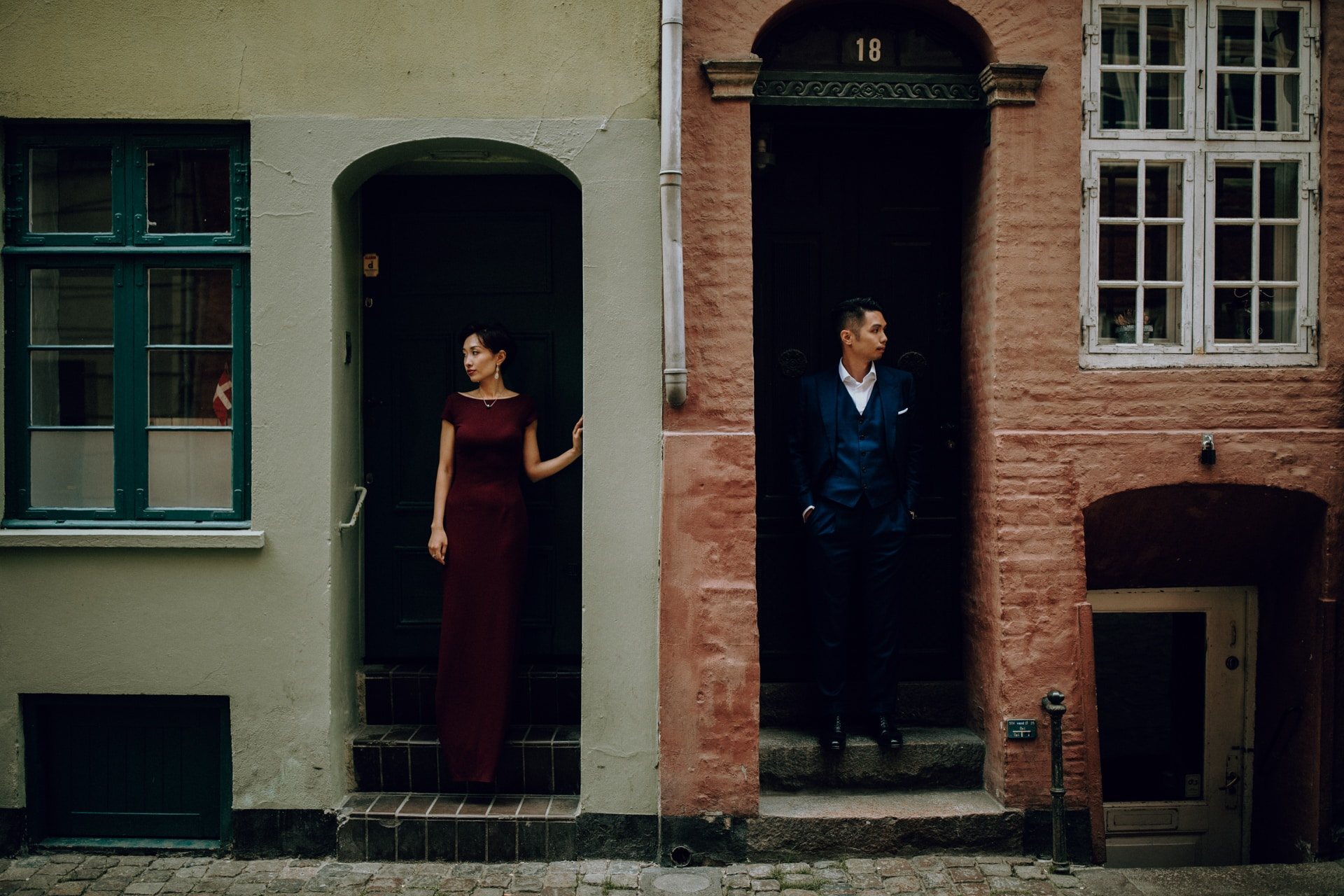 The bride and the groom are each standing in an entrance of an old building.