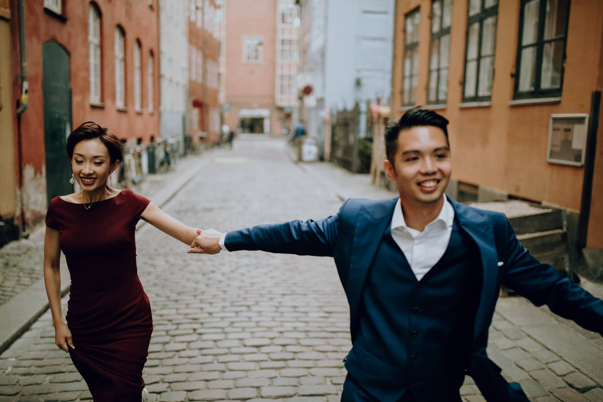 The wedding couple is running through the streets of Copenhagen.