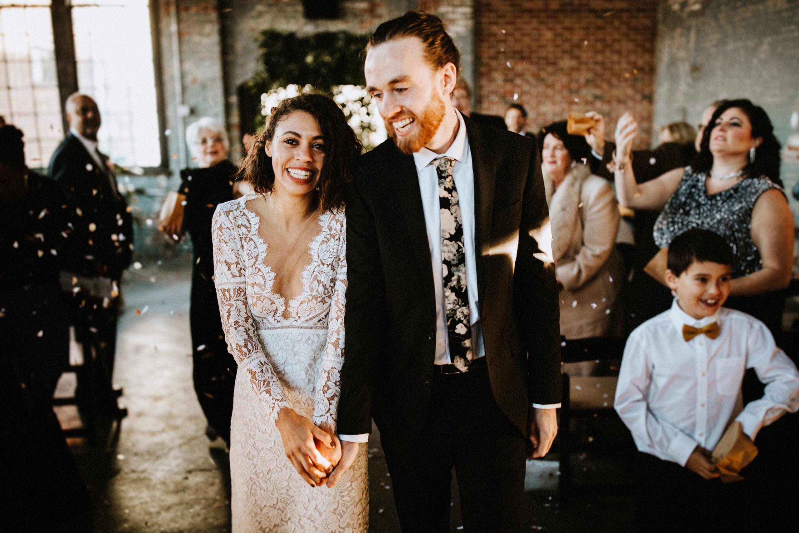 Ein Hochzeitspaar hält sich and den Händen und läuft vom Altar zu den Gästen.