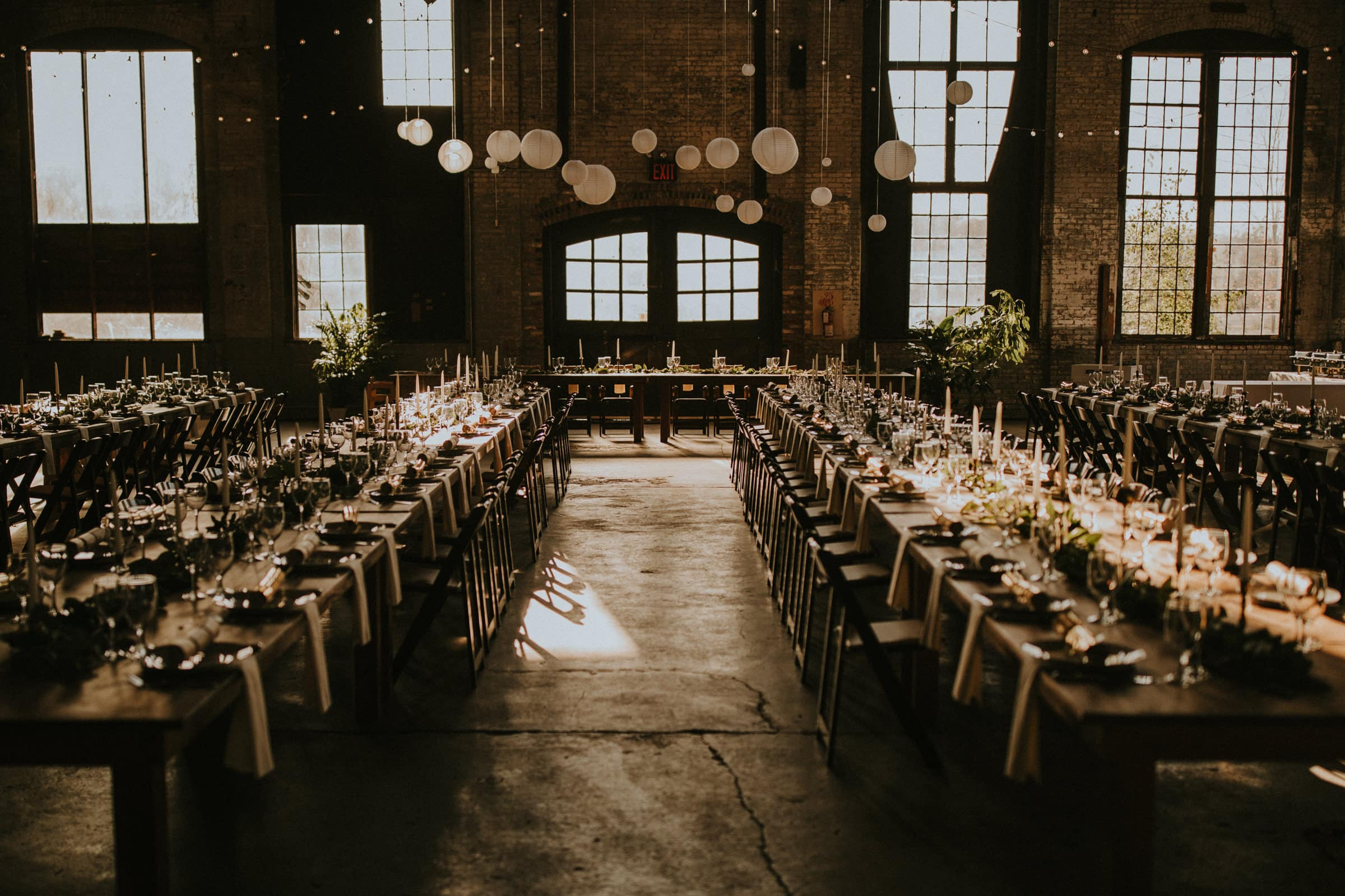 Wedding tables are lined up in a huge industrial hall.