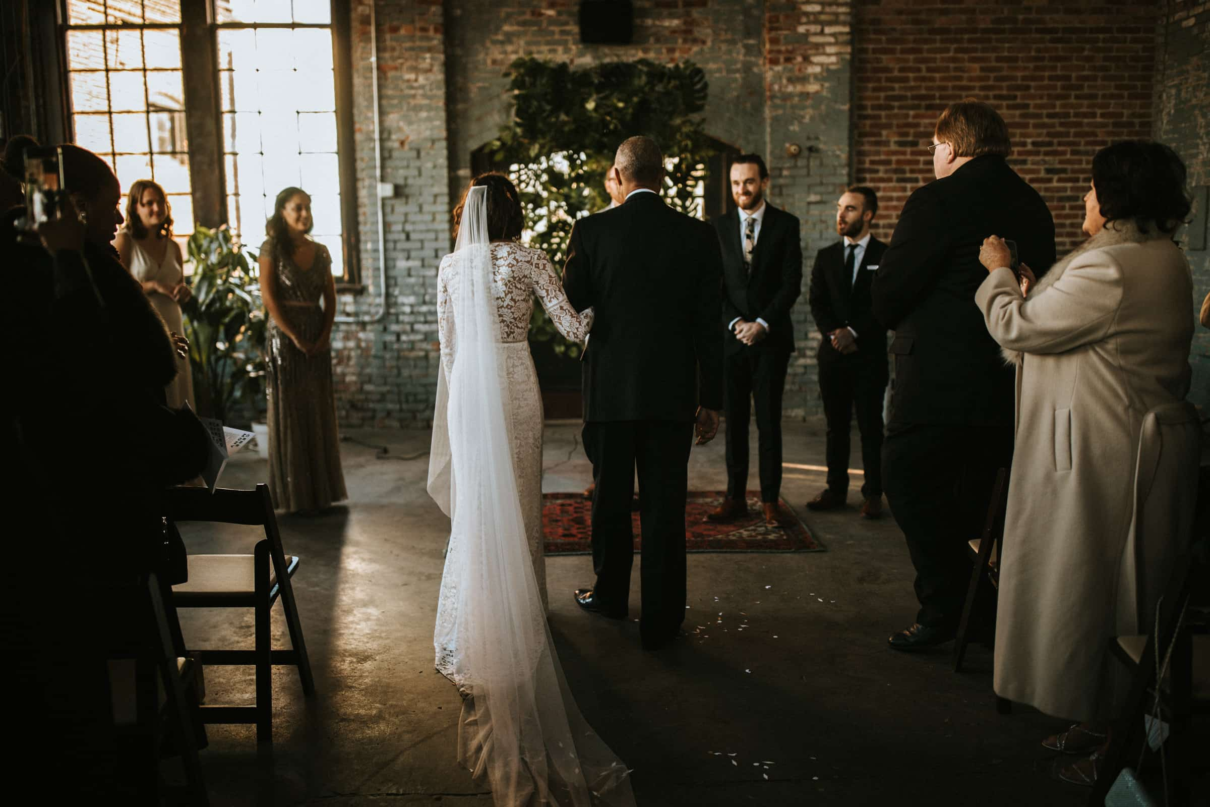 The bride and her father are standing at the end of the aisle.