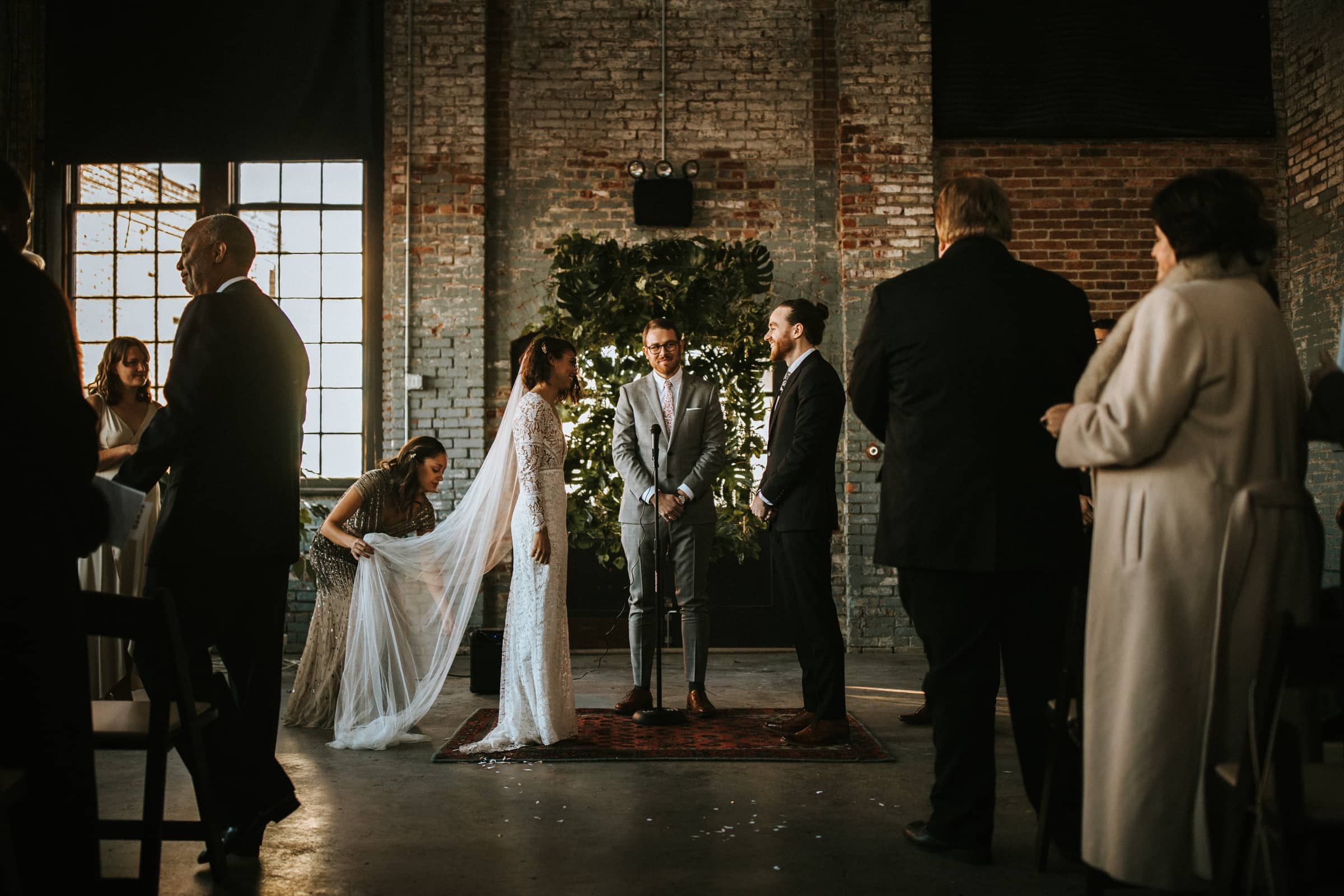 The wedding couple is standing in front of their wedding guests and is about to get married.