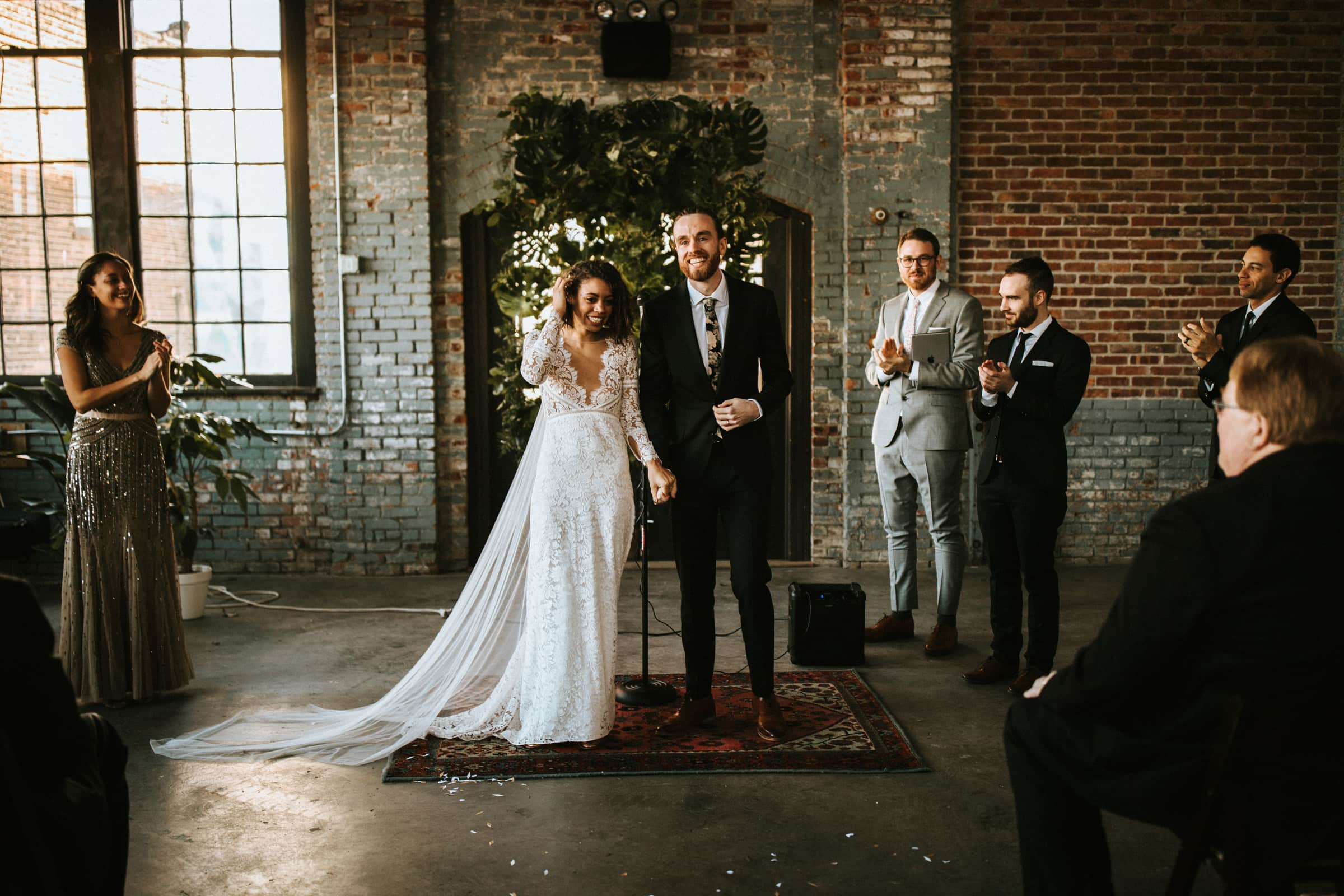 The wedding couple is holding hands, smiling and facing their wedding guests.