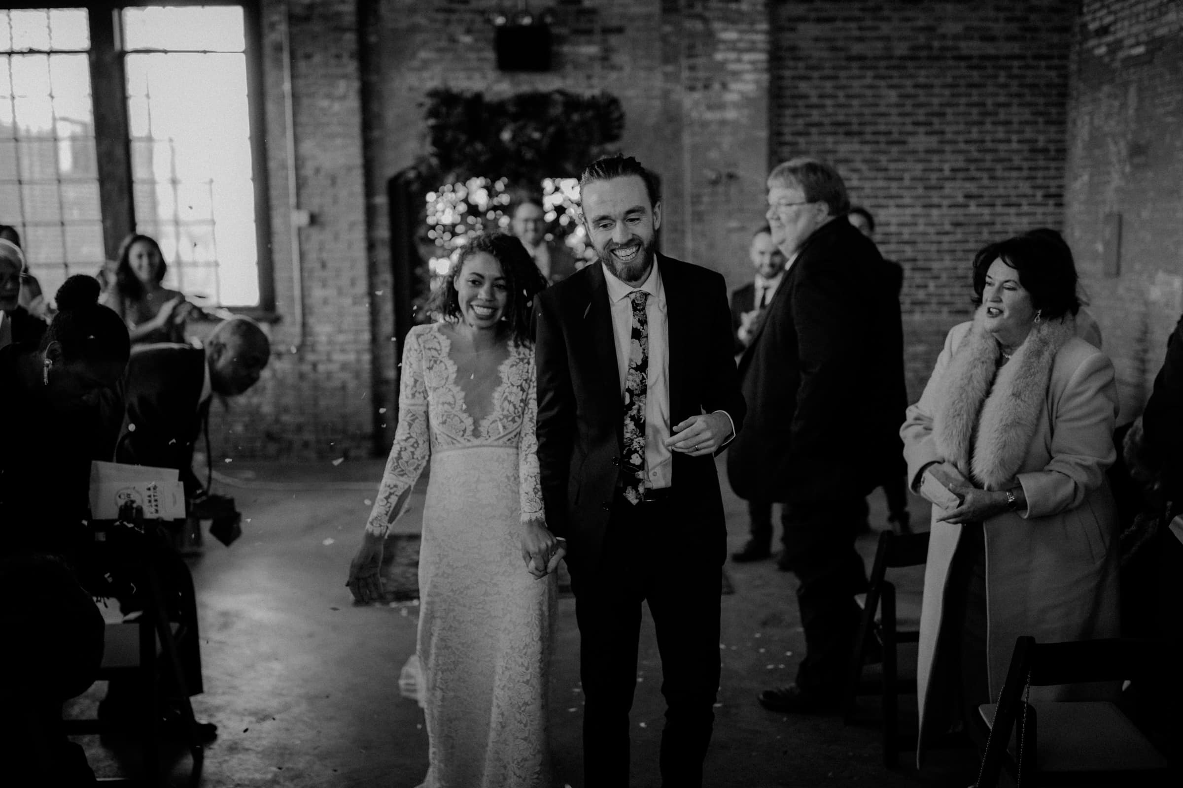 A wedding couple is walking back the aisle together.