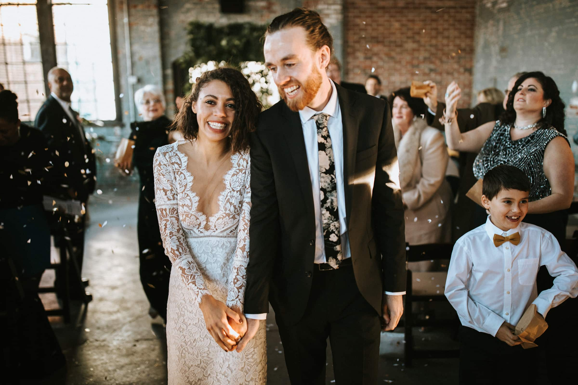 A wedding couple is holding hands and walking back the aisle.