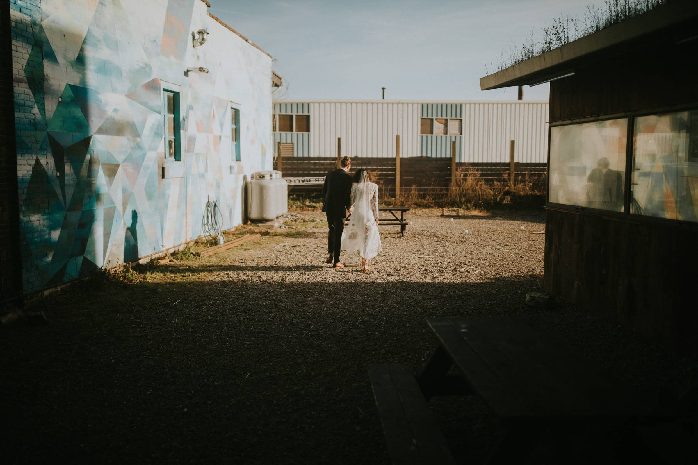 The wedding couple is walking outside next to an industrial building.