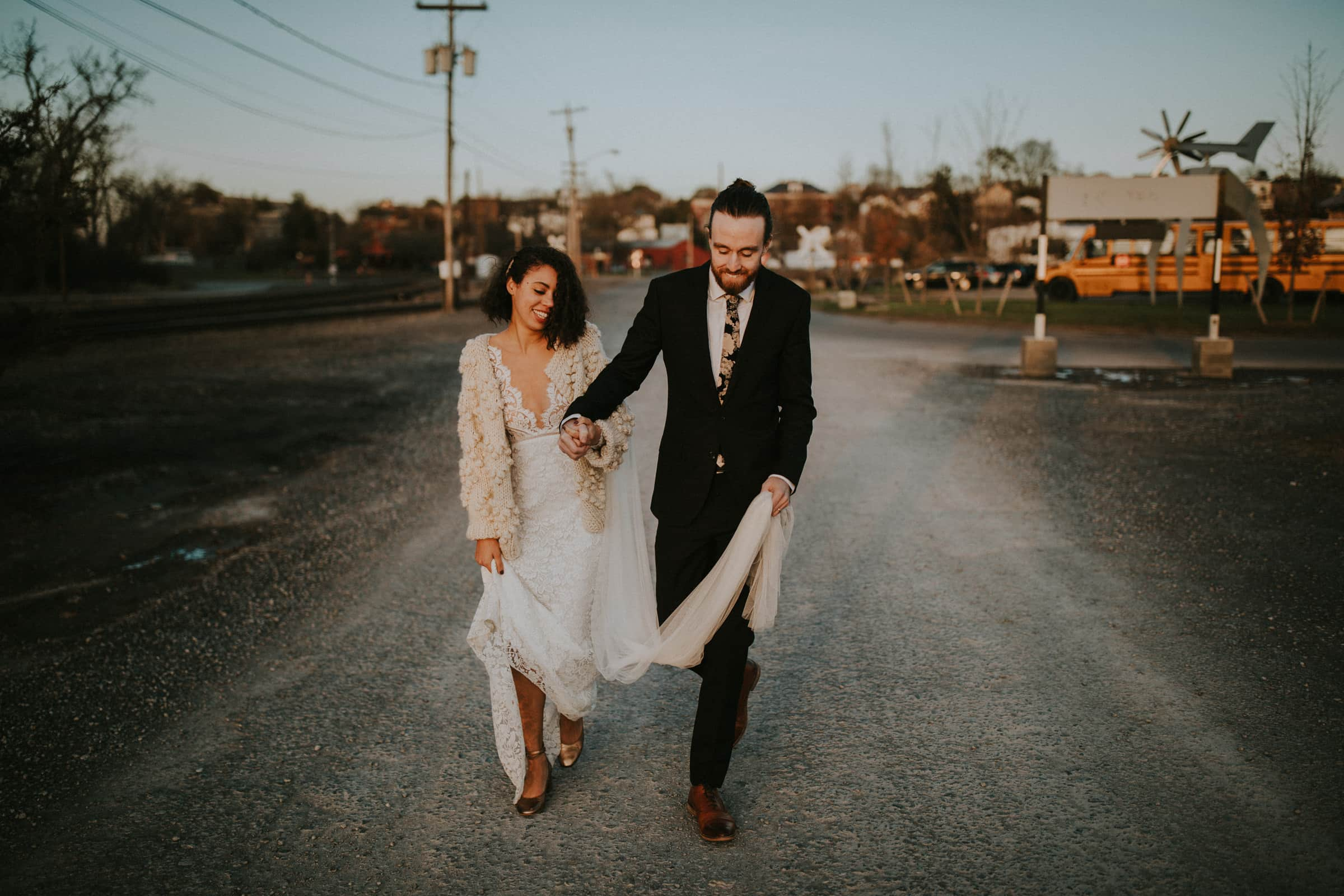the wedding couple is walking down a road next to tram tracks and industrial buildings.