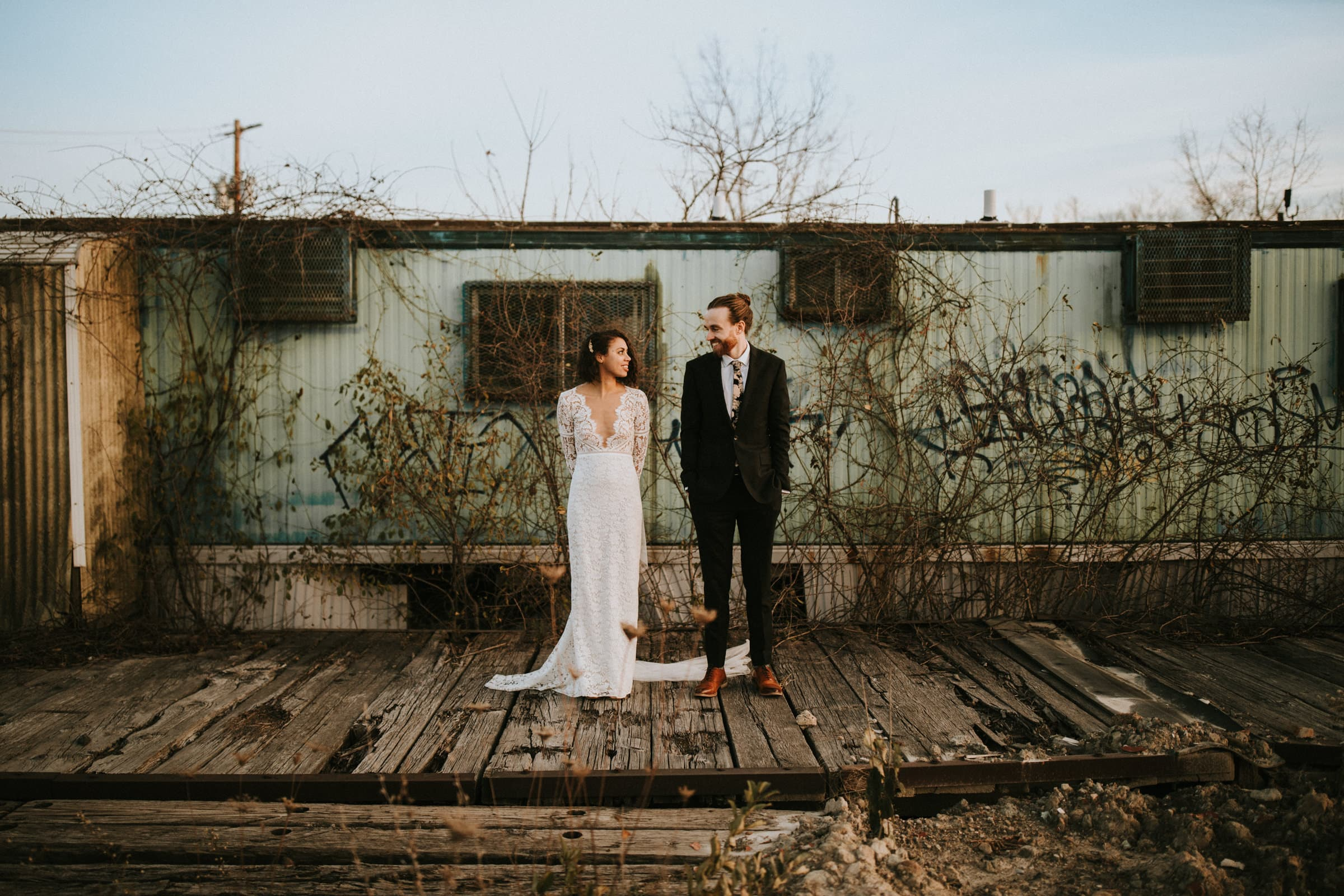 A wedding couple is standing on old tram tracks , in front of an old rustic building.